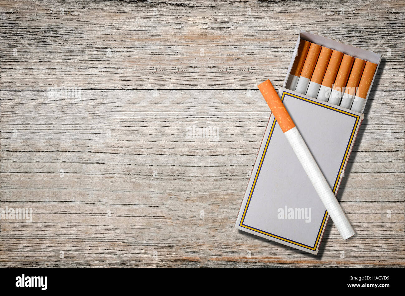 cigarettes in match box on wooden background. - Stock Image