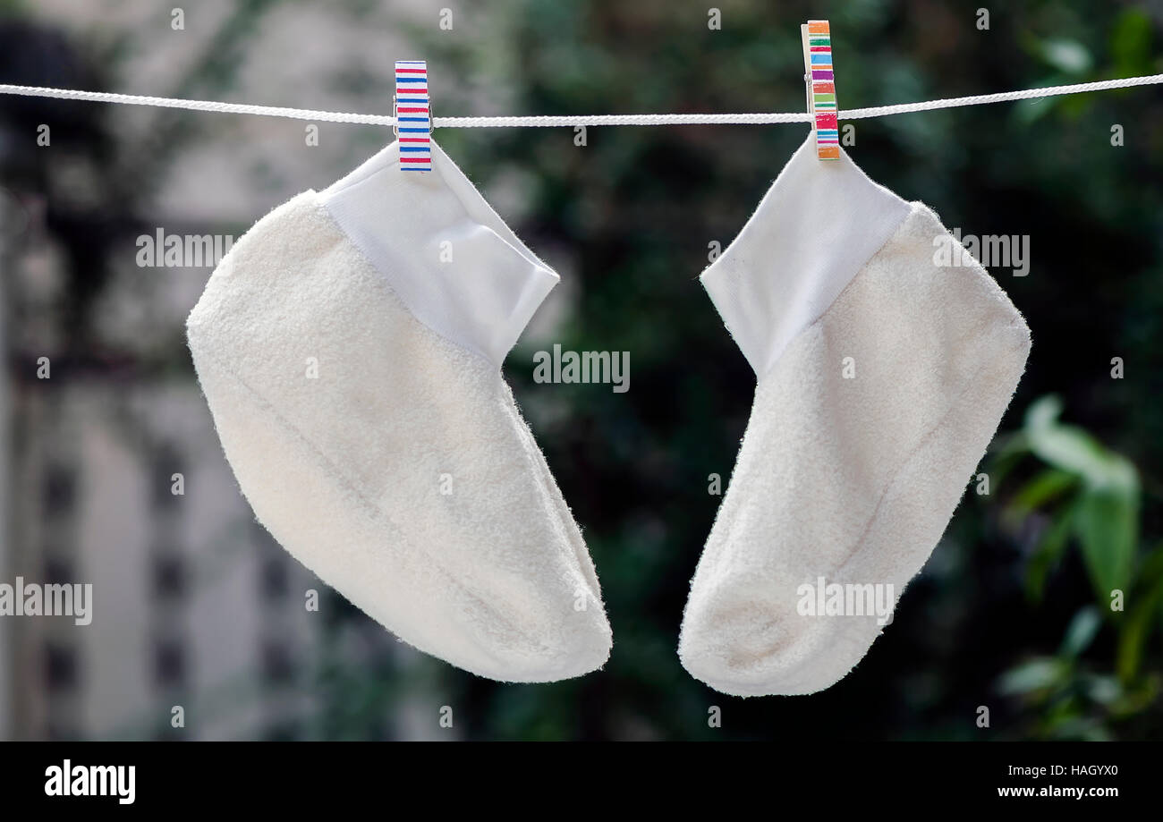 White socks hang on a rope with colorful clothespin . Stock Photo