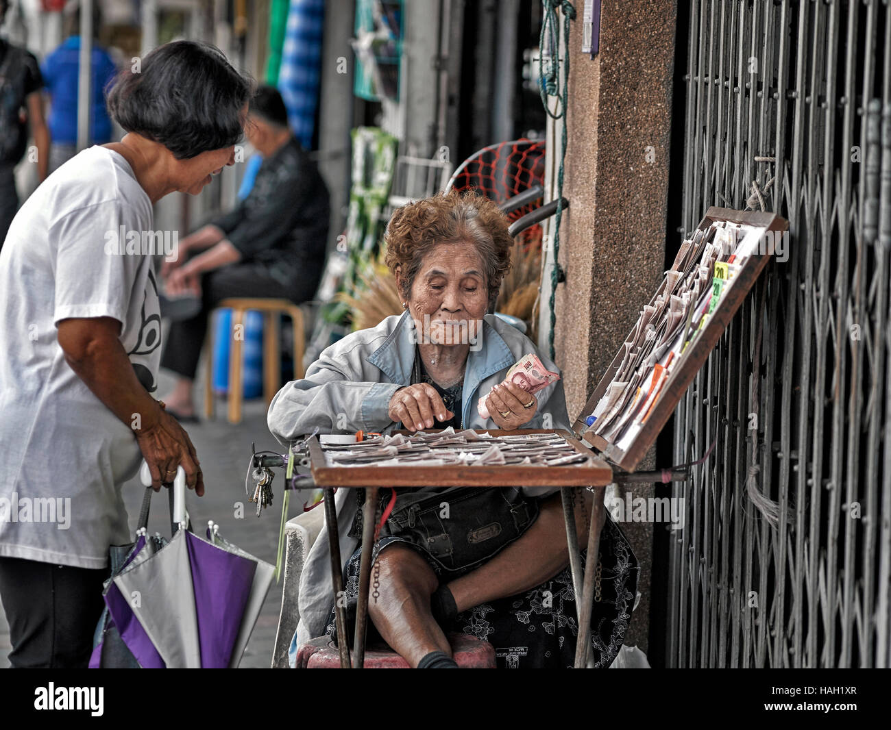 Thai street scene with elderly female lottery vendor with customer. Thailand S. E. Asia - Stock Image