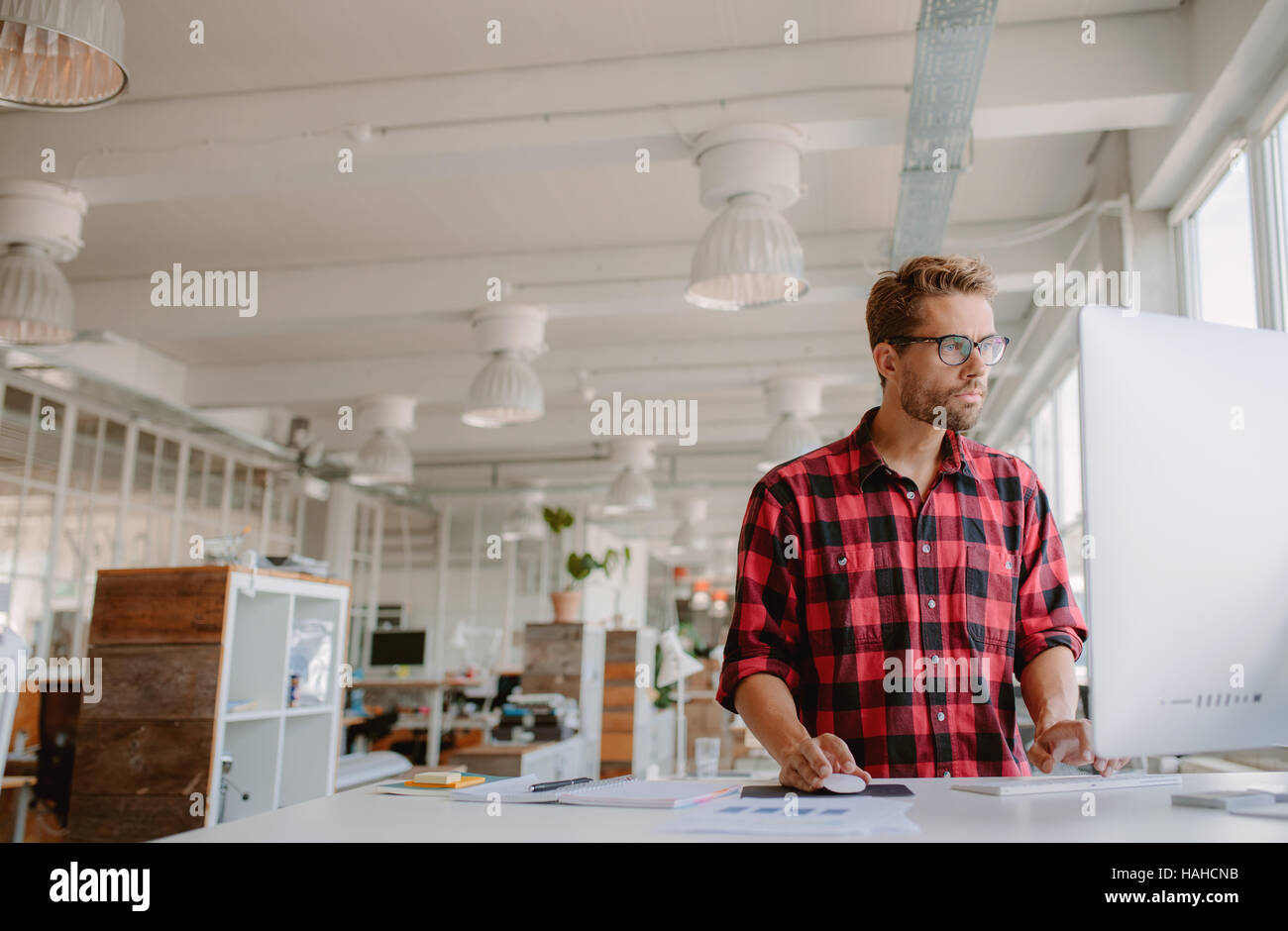Shot of young businessman in casual clothes at modern startup business office space, working on  desktop computer. - Stock Image