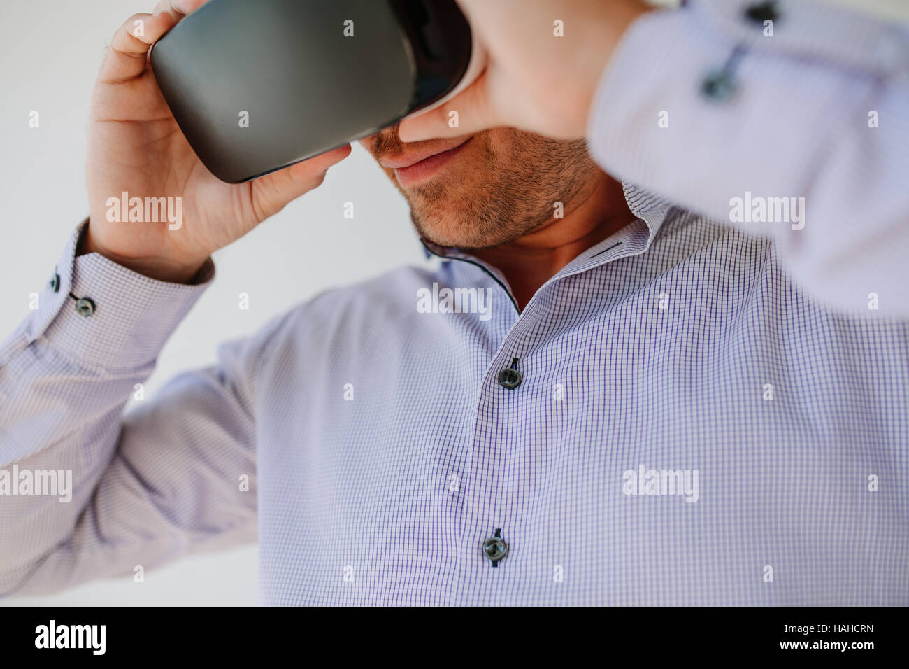 Closeup shot of young man using Virtual Reality glasses. Businessman wearing VR goggles. - Stock Image