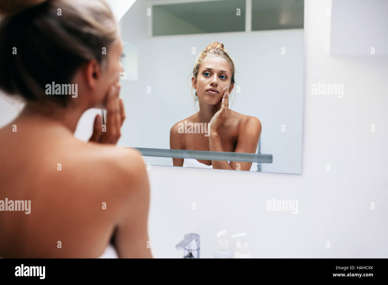 Beautiful young woman in bathroom looking in to mirror and applying moisturizer on face . Beauty treatment in bathroom. - Stock Image