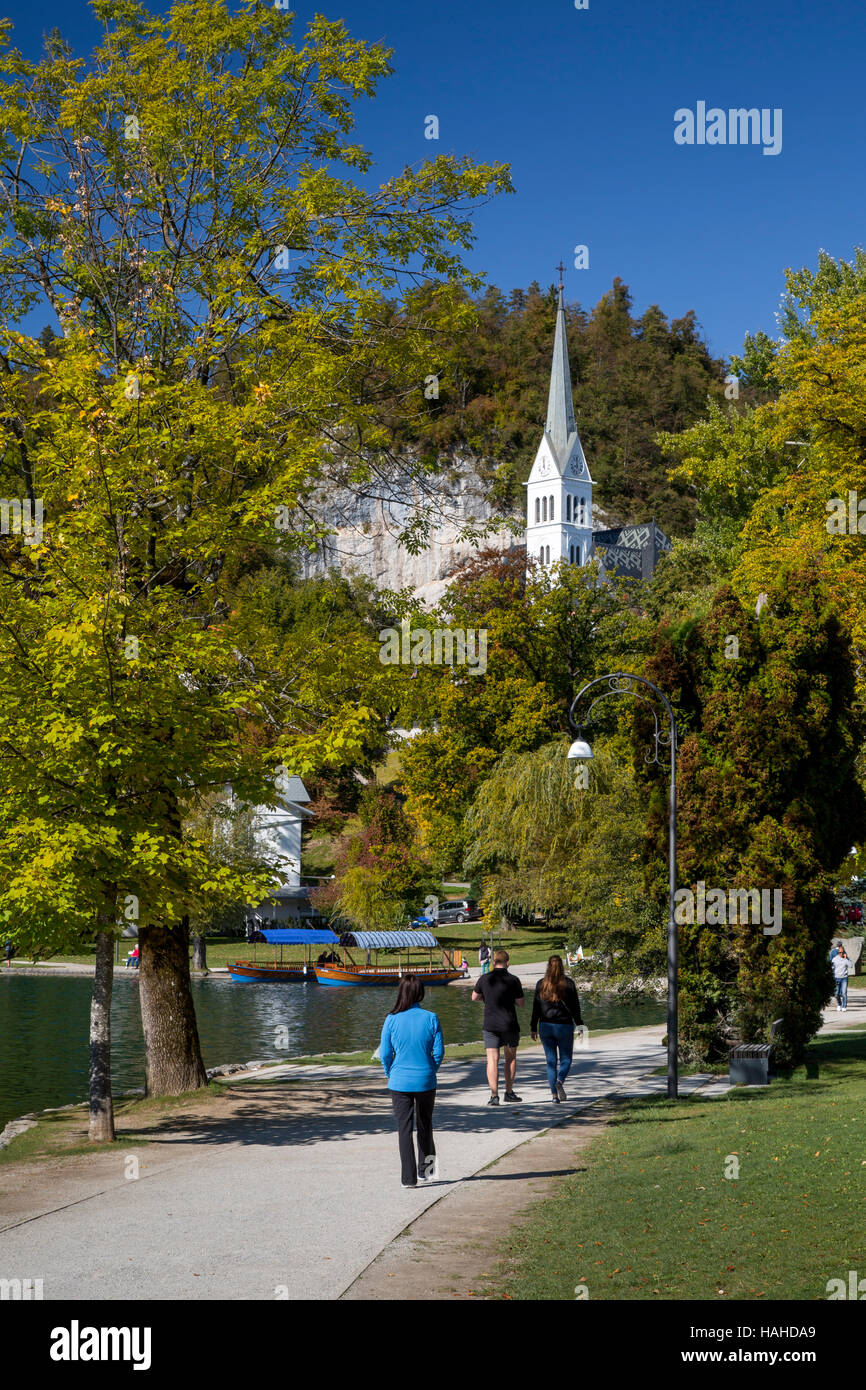 Walkway around Lake Bled with the tower of St Martin Parish Church, Bled, Upper Carniola, Slovenia - Stock Image