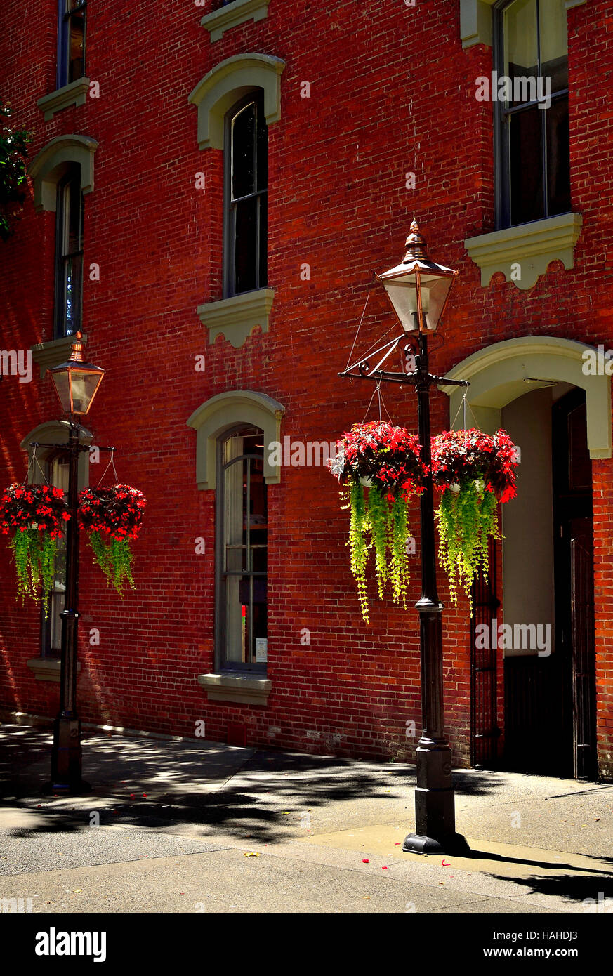 Street lights with flower baskets in front of a brick building - Stock Image