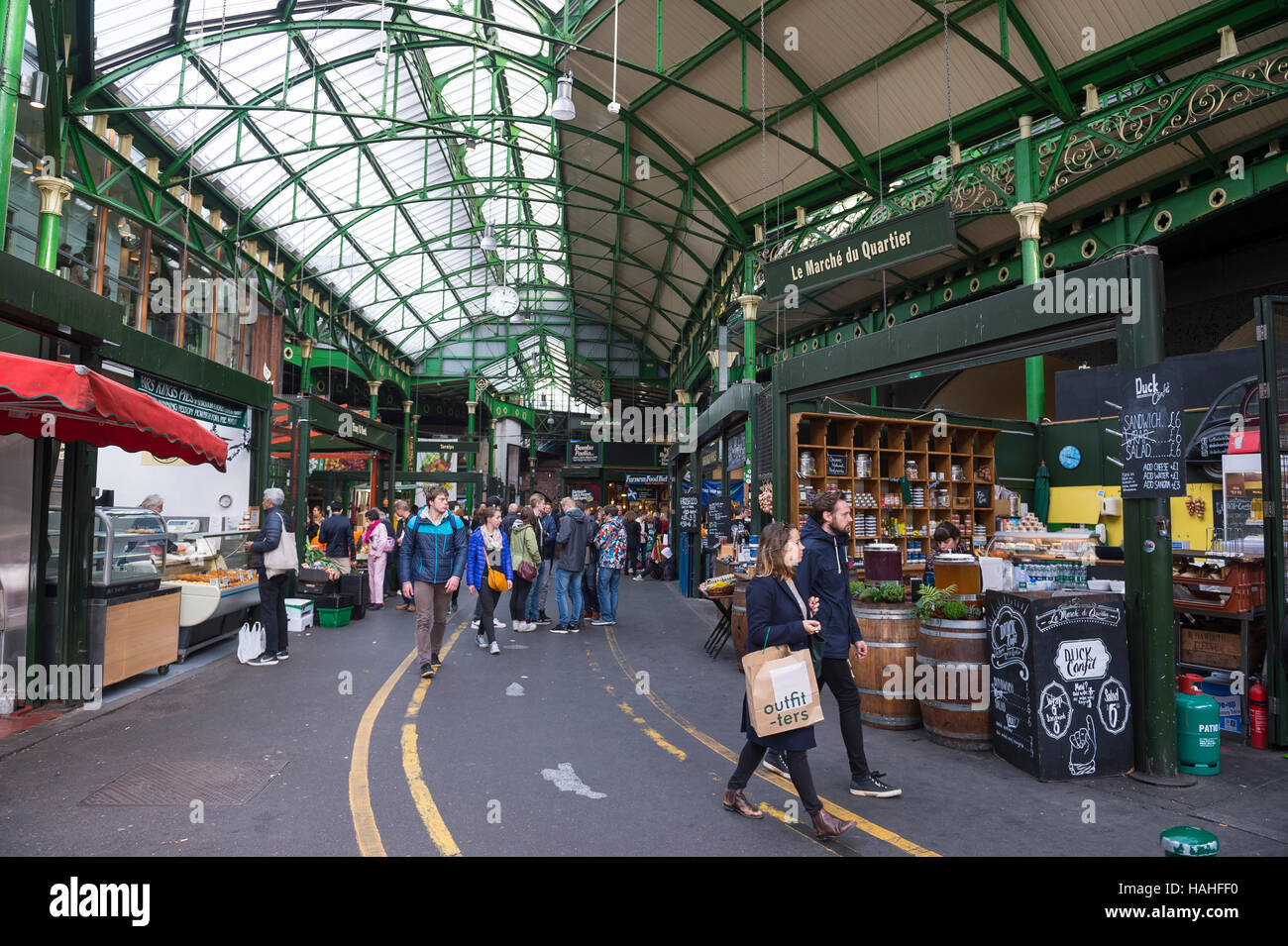 LONDON - OCTOBER 31, 2016: Visitors browse the specialty food stalls at Borough Market, one of the largest and oldest - Stock Image