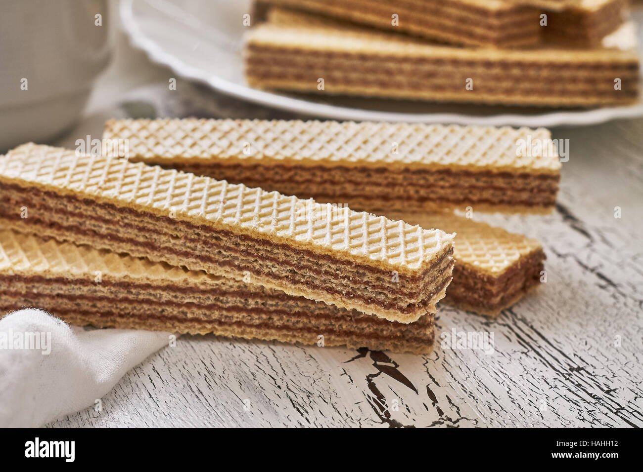 Wafer biscuits with chocolate cream on white rustic wooden background - Stock Image