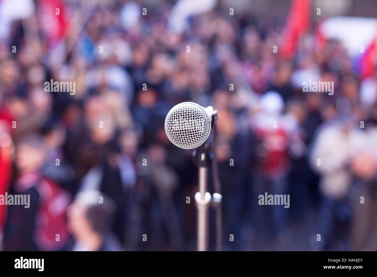 Street protest. Political rally. Microphone in focus against blurred crowd. - Stock Image