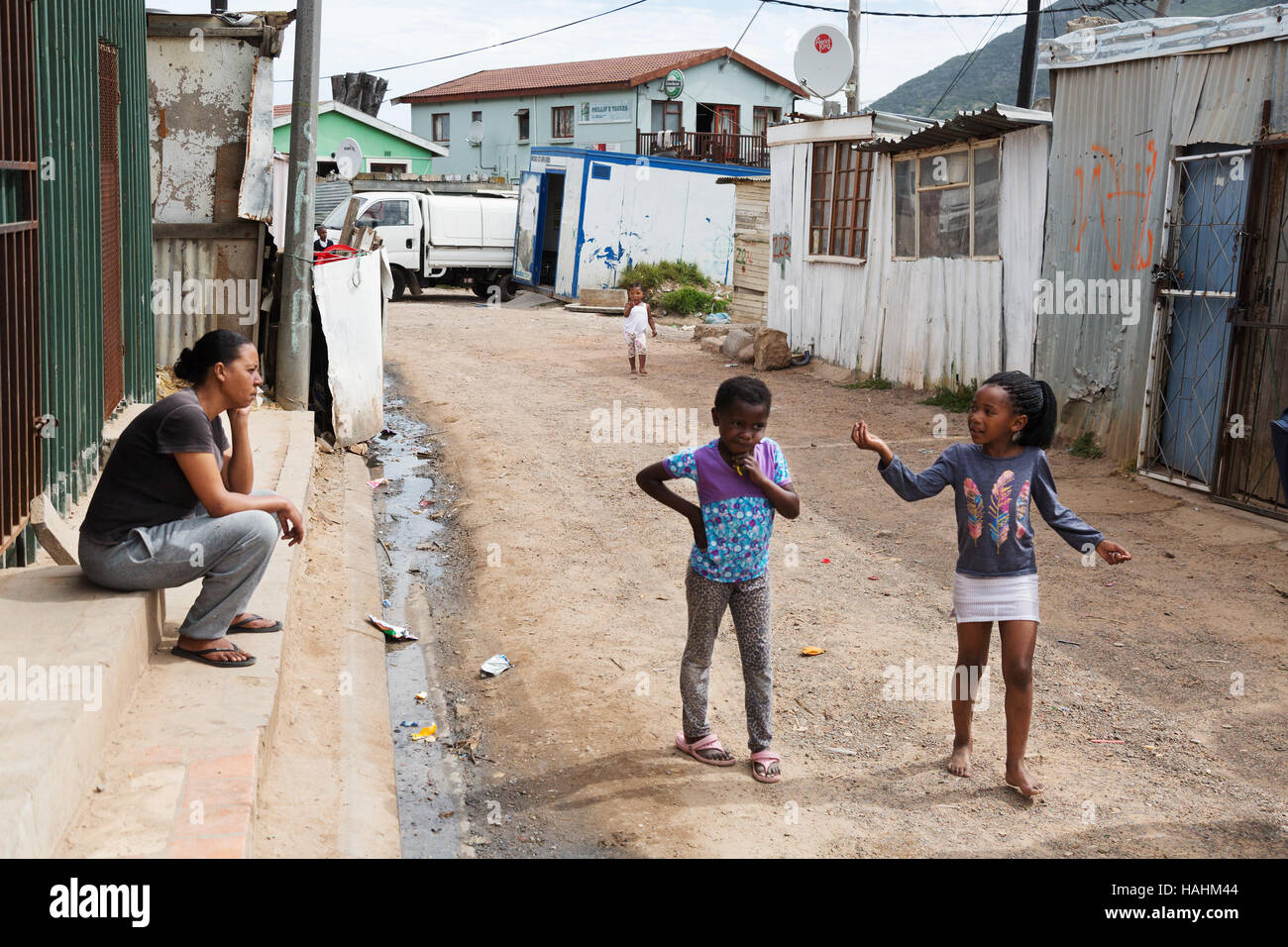 two children talking to an adult on the street, Imizamo Yethu township, Cape Town, South Africa Stock Photo