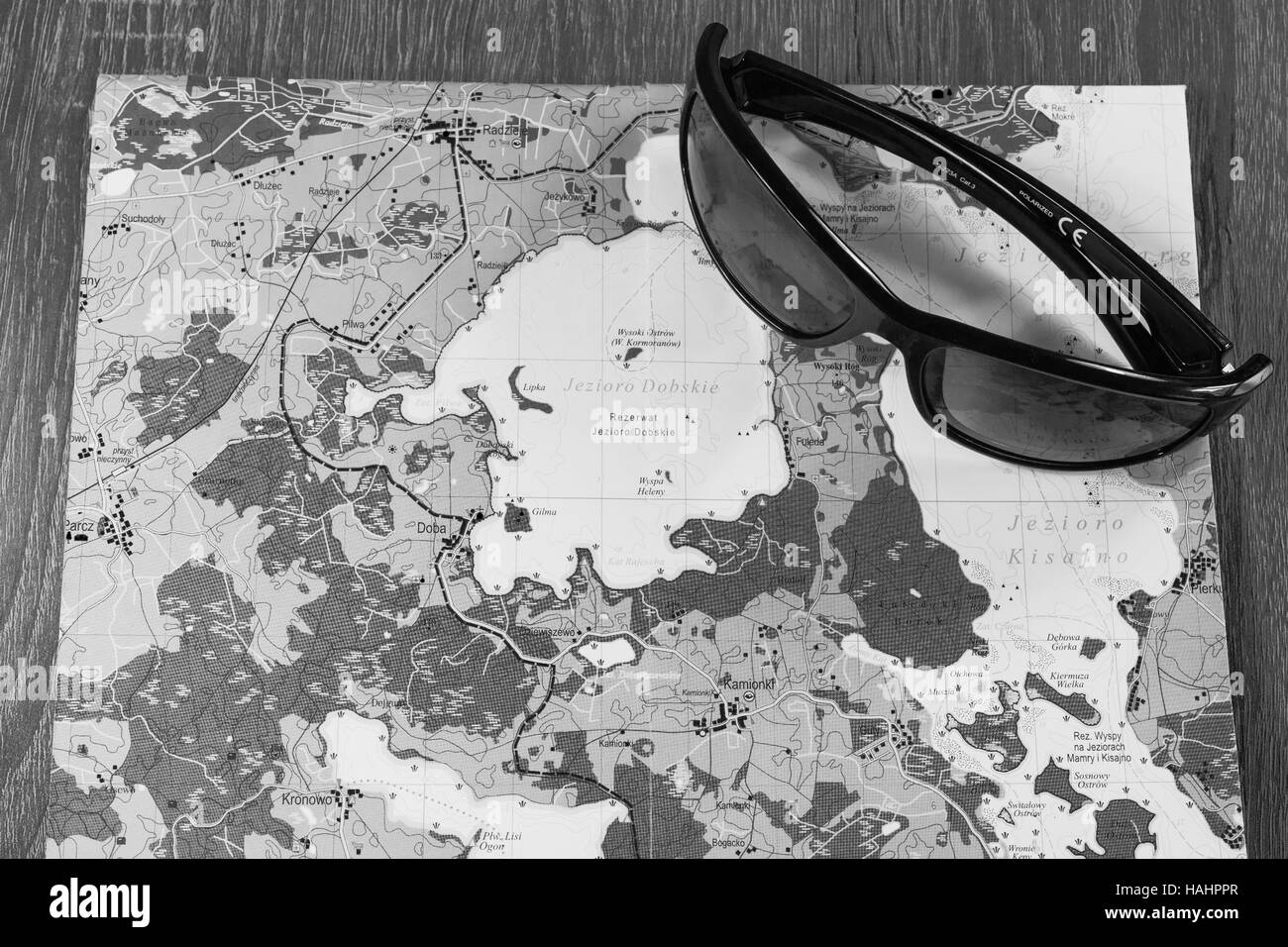 Eyewear placed on the map. Sunglasses with a map of specific Polish region. Glasses and map on a table - Stock Image