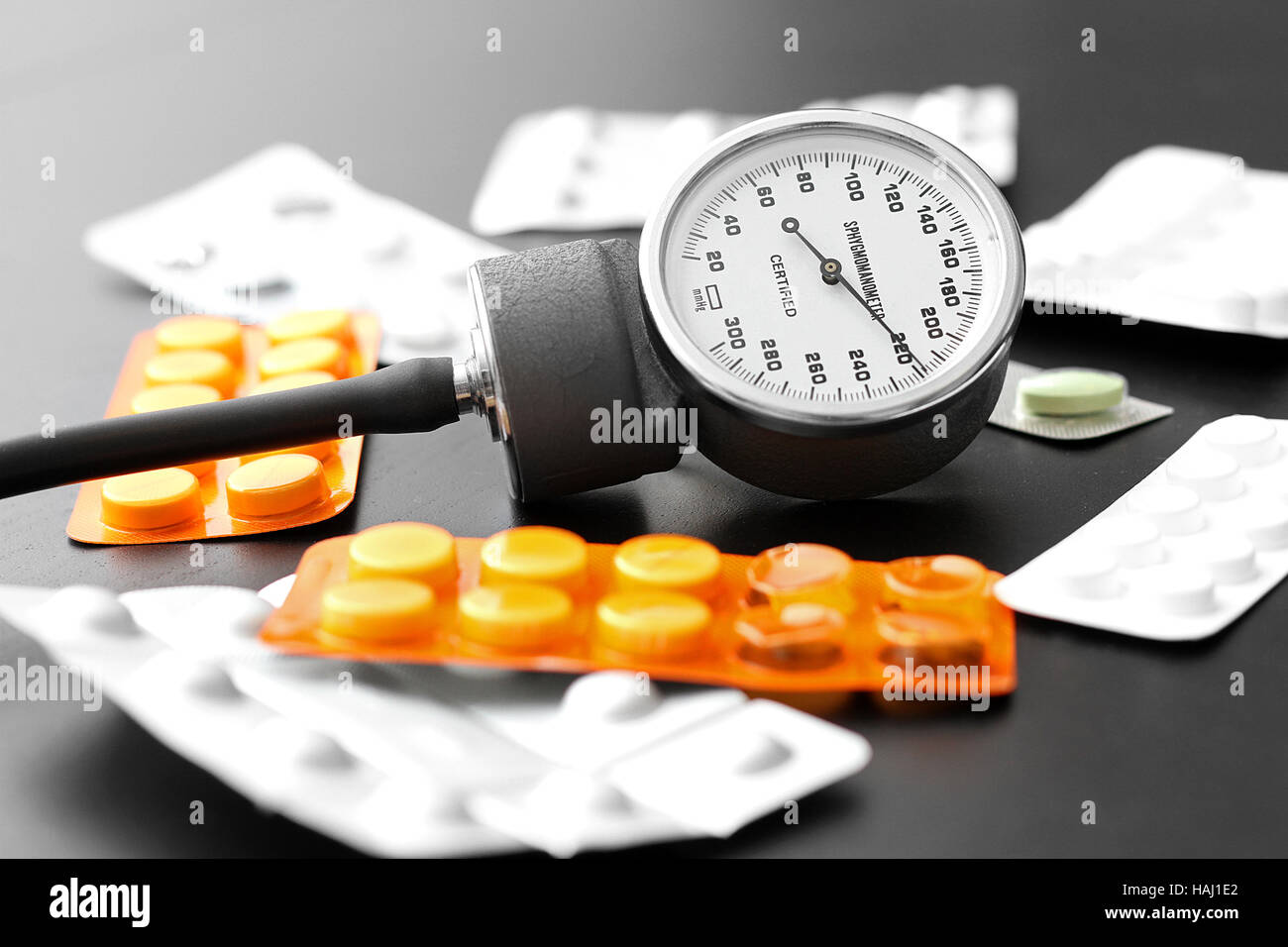 blood pressure meter and pills on the table - Stock Image