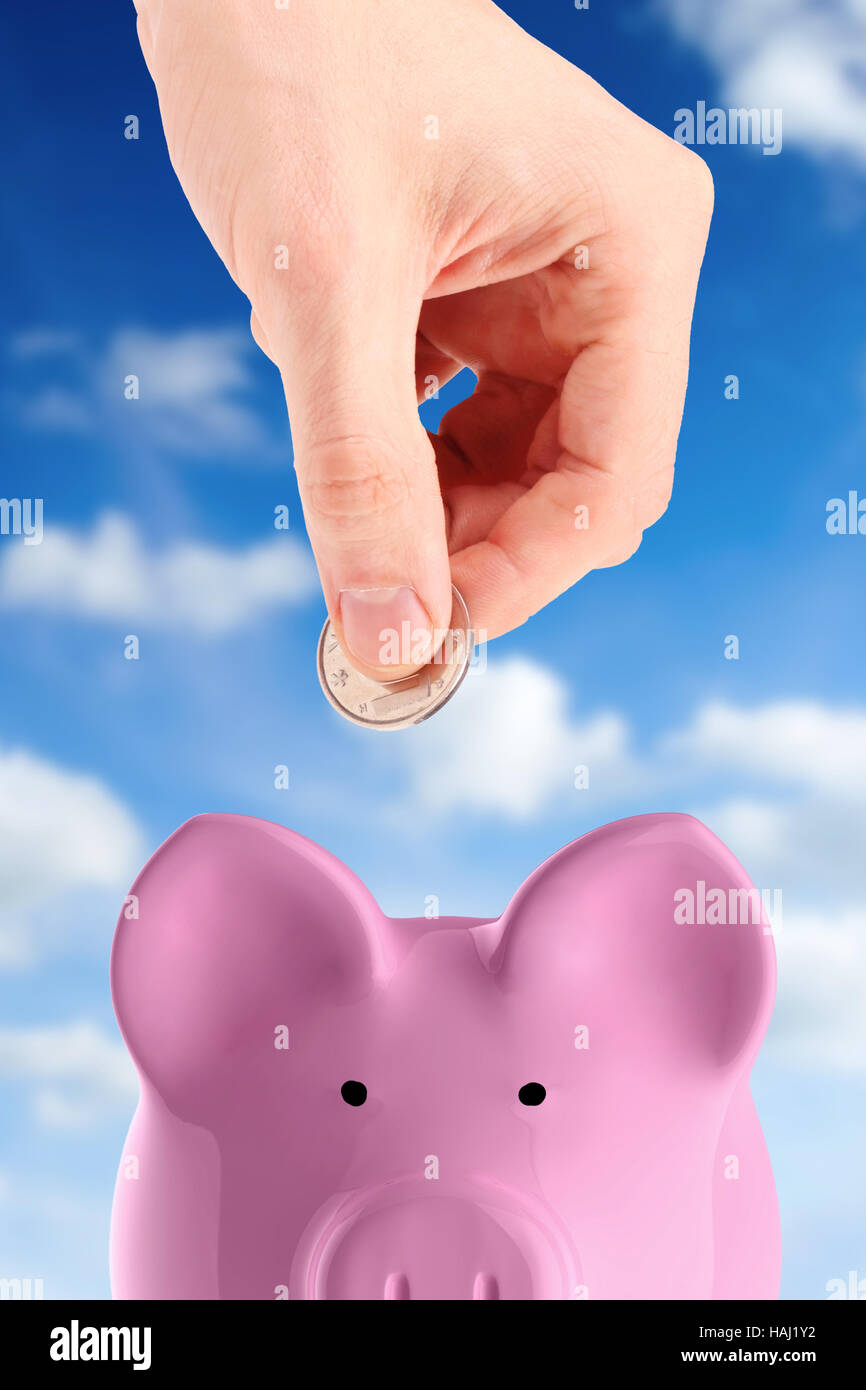 hand putting a coin into piggy bank - Stock Image