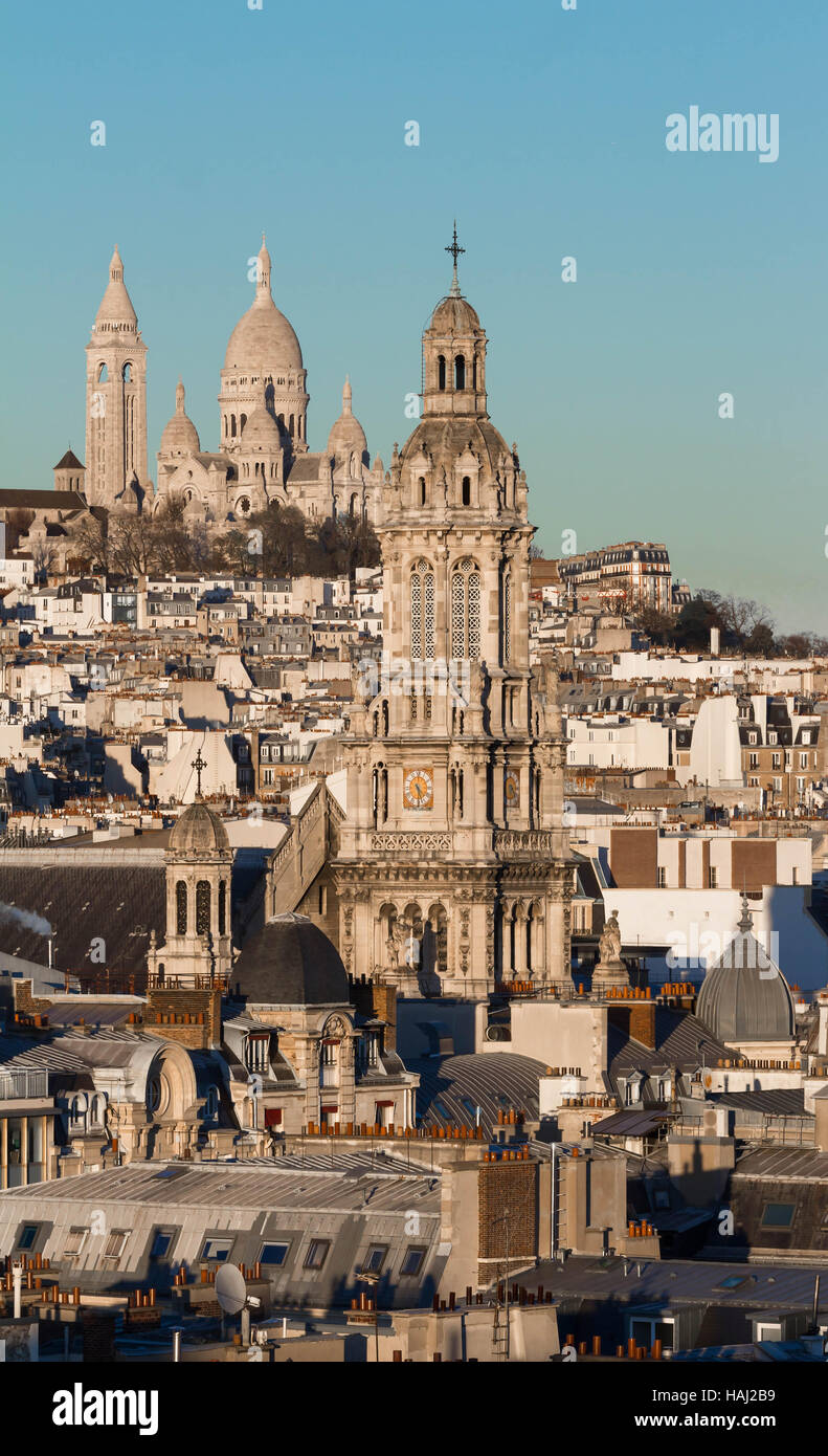 The Saint Trinity church and Sacre Coeur basilica in the background, Paris, France. - Stock Image