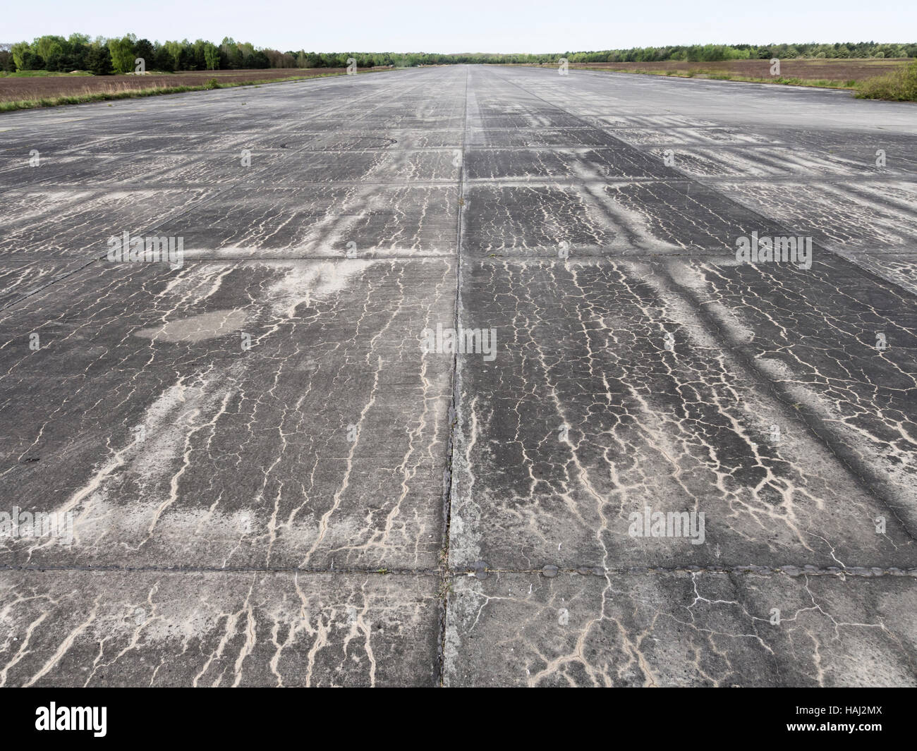 Abandoned concrete airport runway and airfield, fallow land - Stock Image
