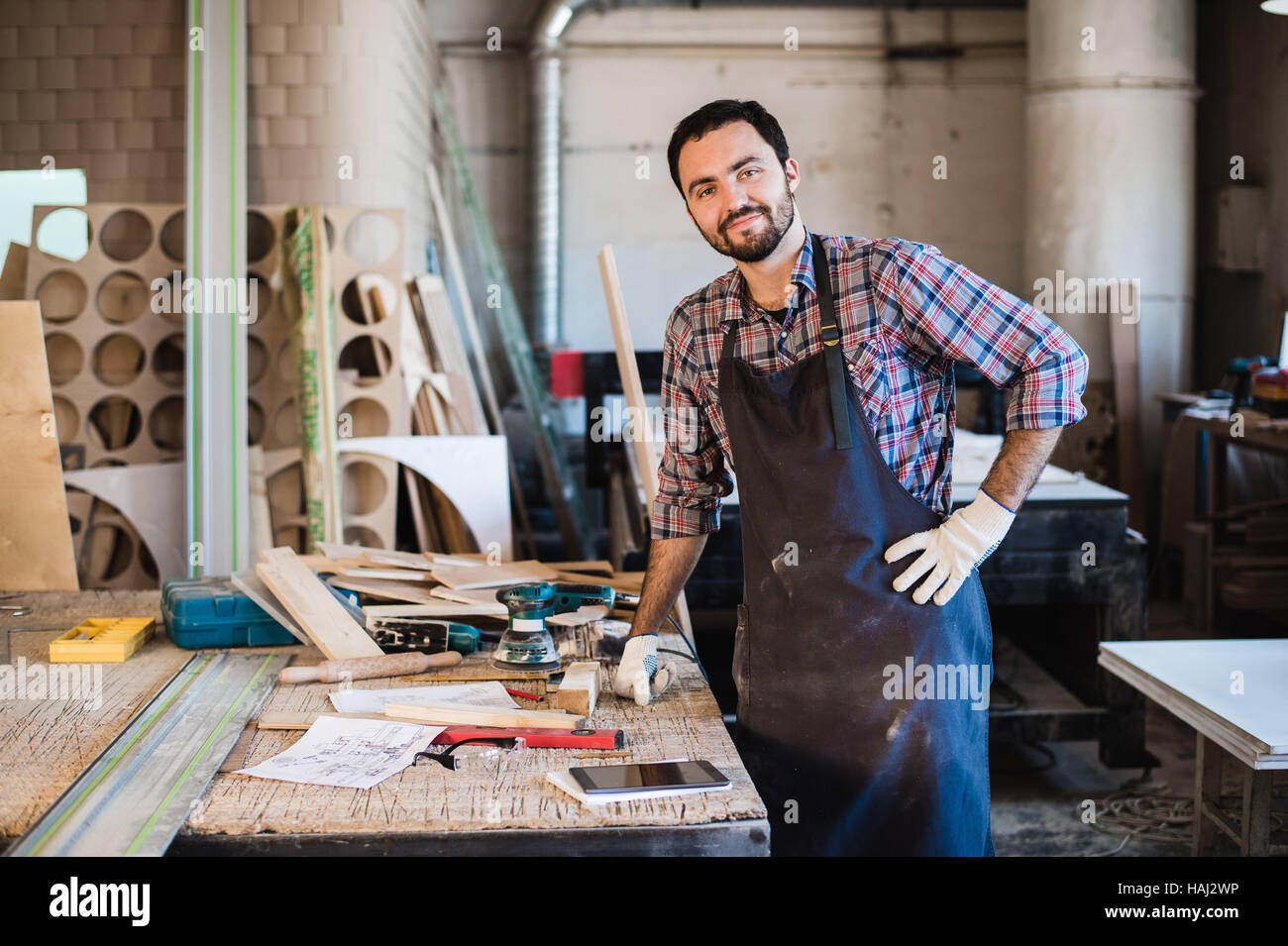 Carpenter working carefully looking at the plans - Stock Image
