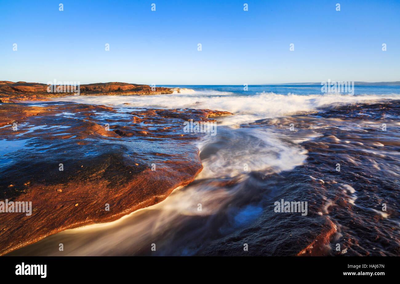 Waves breaking on the rocky sandstone shoreline below Red Bluff in Kalbarri National Park - Stock Image