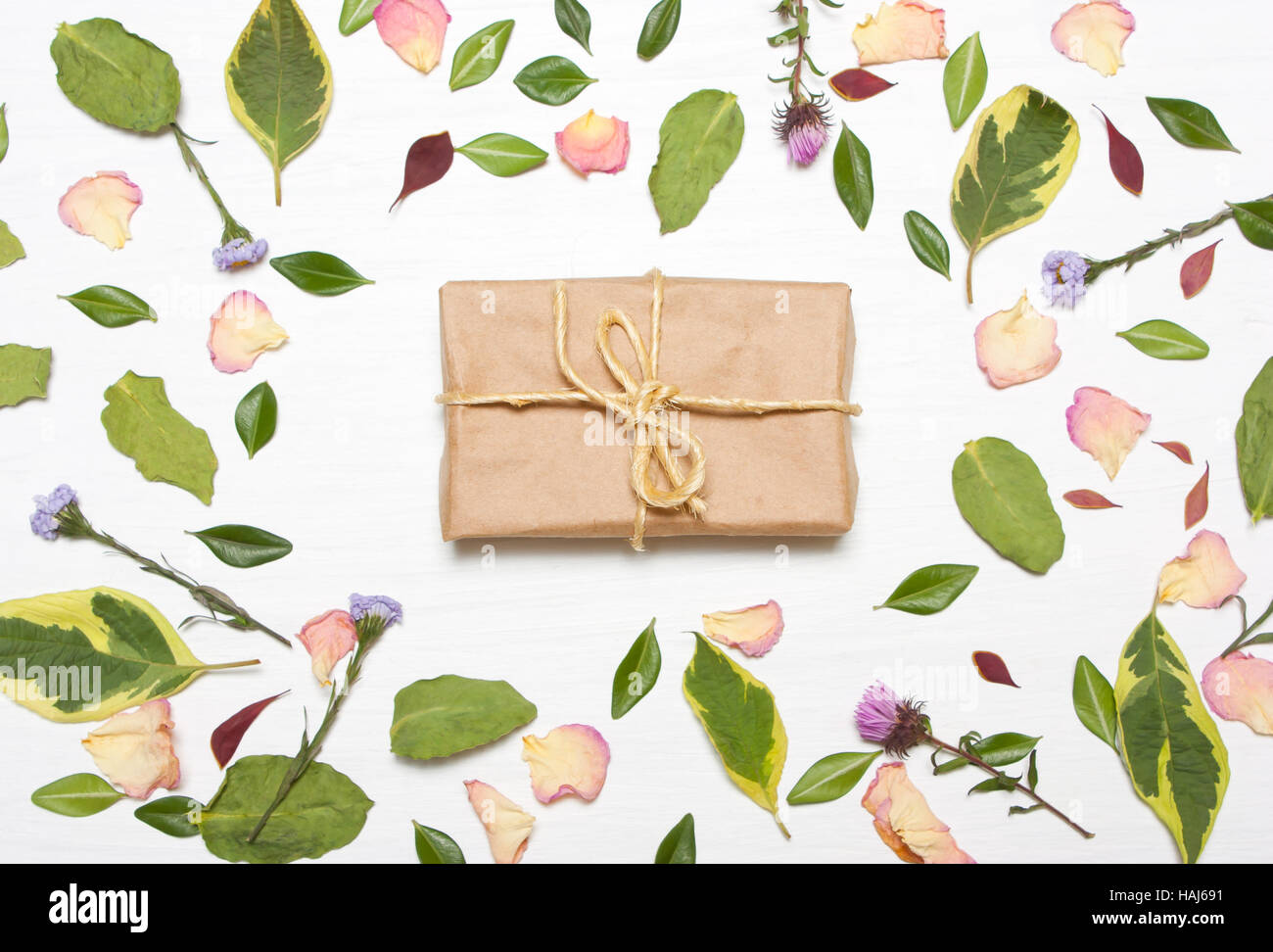 Gift in the frame from flowers and leaves.The concept congratulations.Type flat, top view - Stock Image