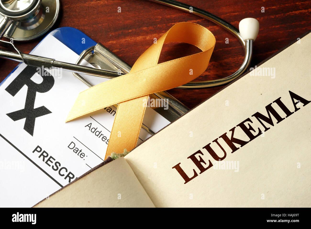 Leukemia written on a page and  orange awareness ribbon. - Stock Image