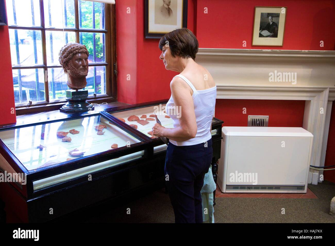 Woman tourist looking at artefacts in a glass cabinet. Chesters Roman Fort and Museum. Chollerford, Hexham, Northumberland, - Stock Image