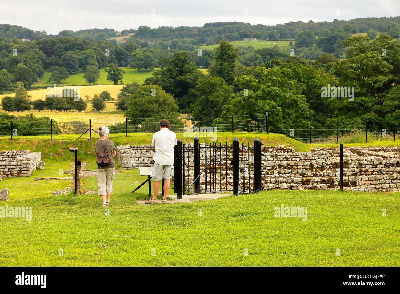 Couple of retired tourists looking at the barracks ruins. Chesters Roman Fort and Museum. Chollerford, Hexham, Northumberland, - Stock Image