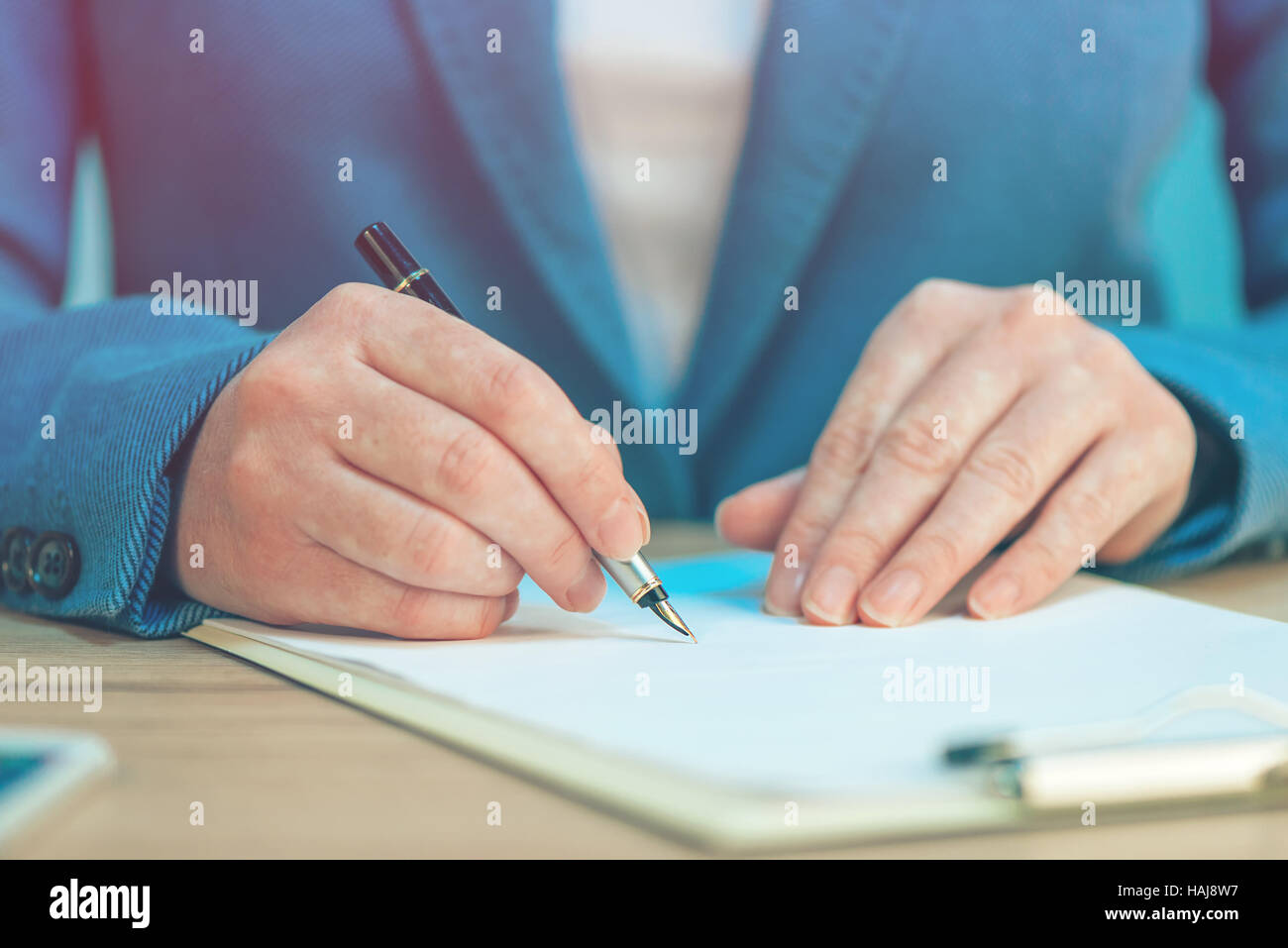 Close up of female hands writing signature on business agreement contract in the office - Stock Image