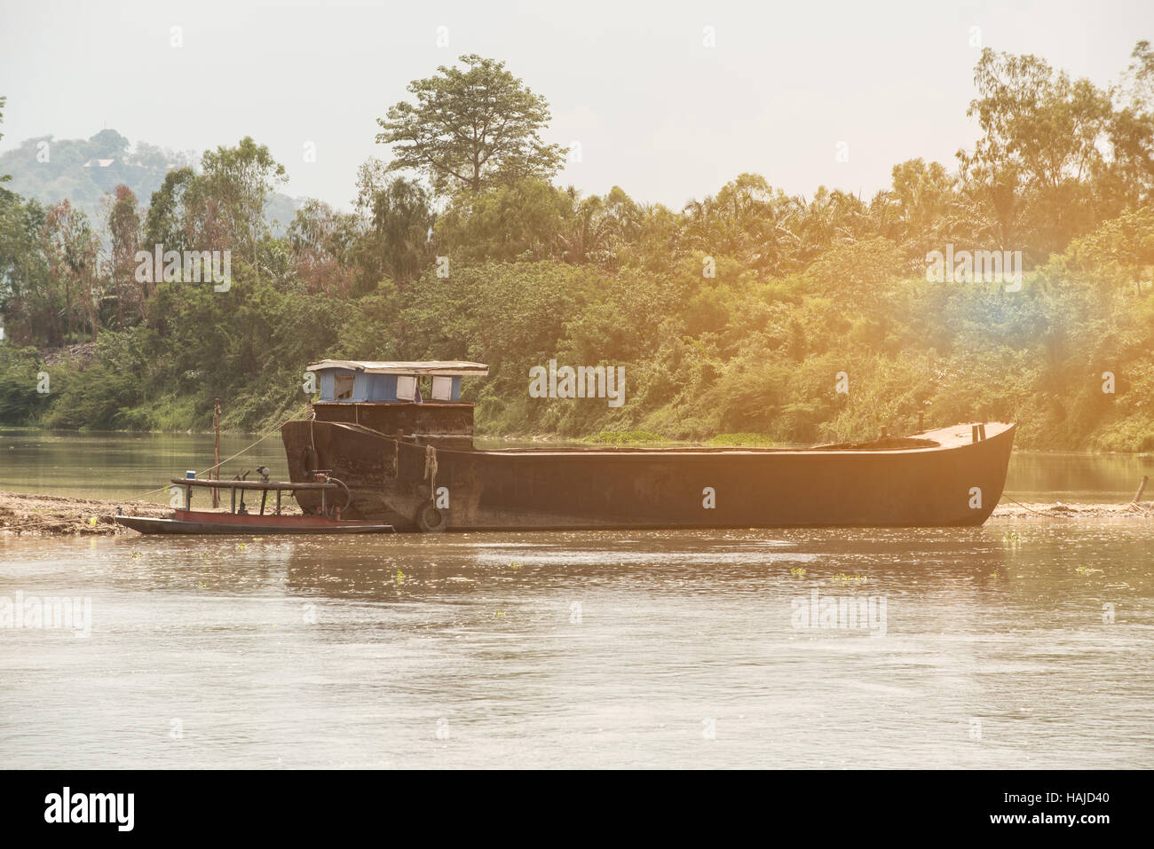 Sand boat with small boat park on river bank in construction site.sands explotation make change flow and environment - Stock Image