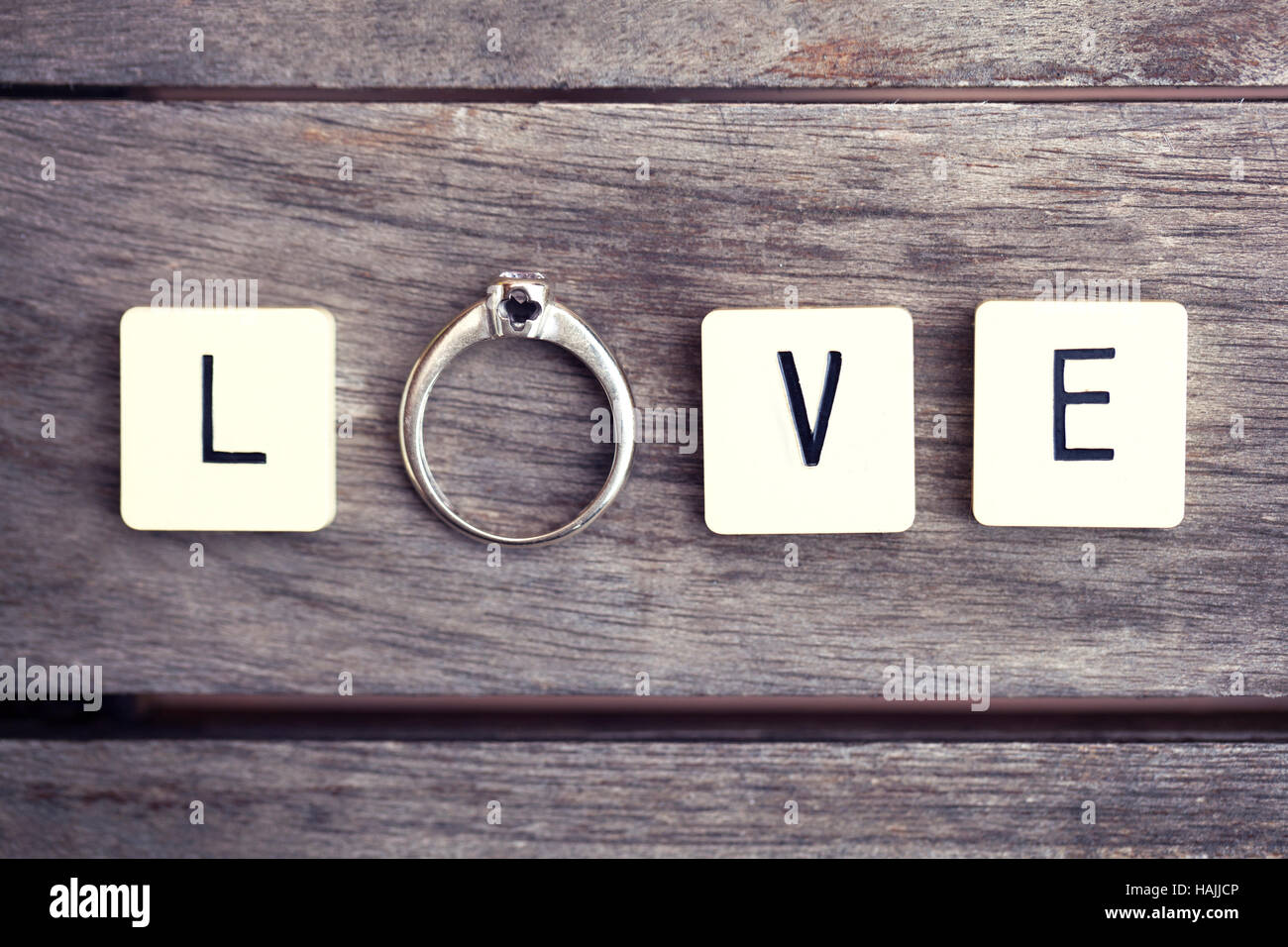 Letter tiles and ring spelling the word 'LOVE'. Conceptual picture for love, wedding, mariage, engagement, - Stock Image