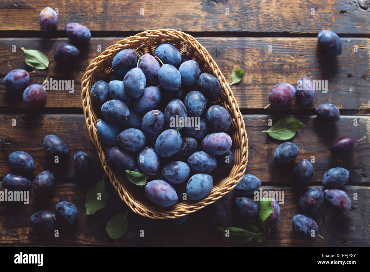 Freshly picked organic plums on a wooden table - Stock Image