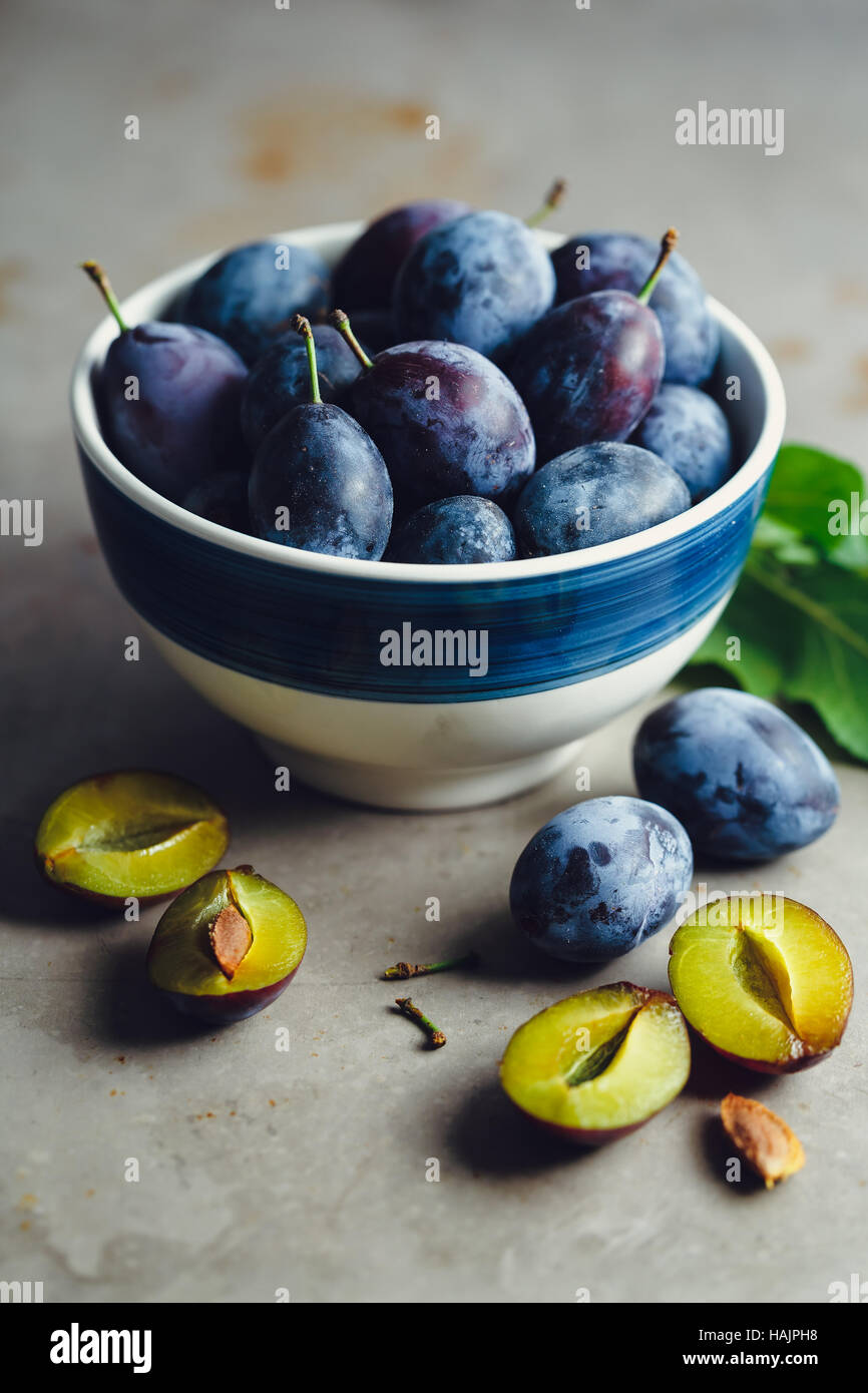 Freshly picked organic plums in bowl on table - Stock Image