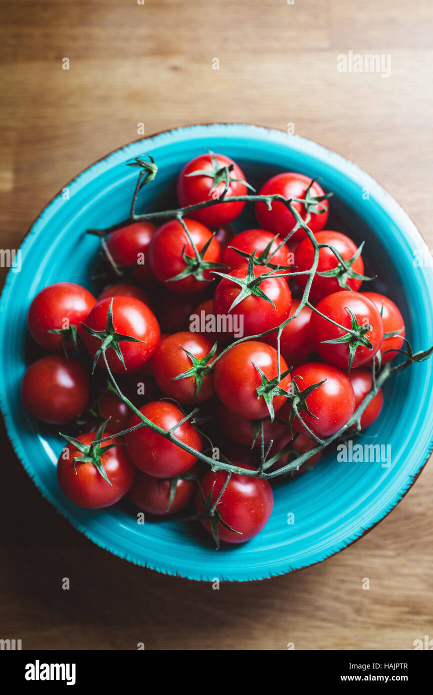 Cherry tomatoes on the vine. Blue bowl of cherry tomatoes on wooden table. - Stock Image