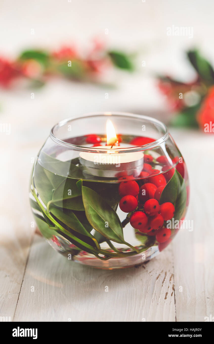 Christmas Table Decoration. Glass vase with holly berries and white floating candle. - Stock Image