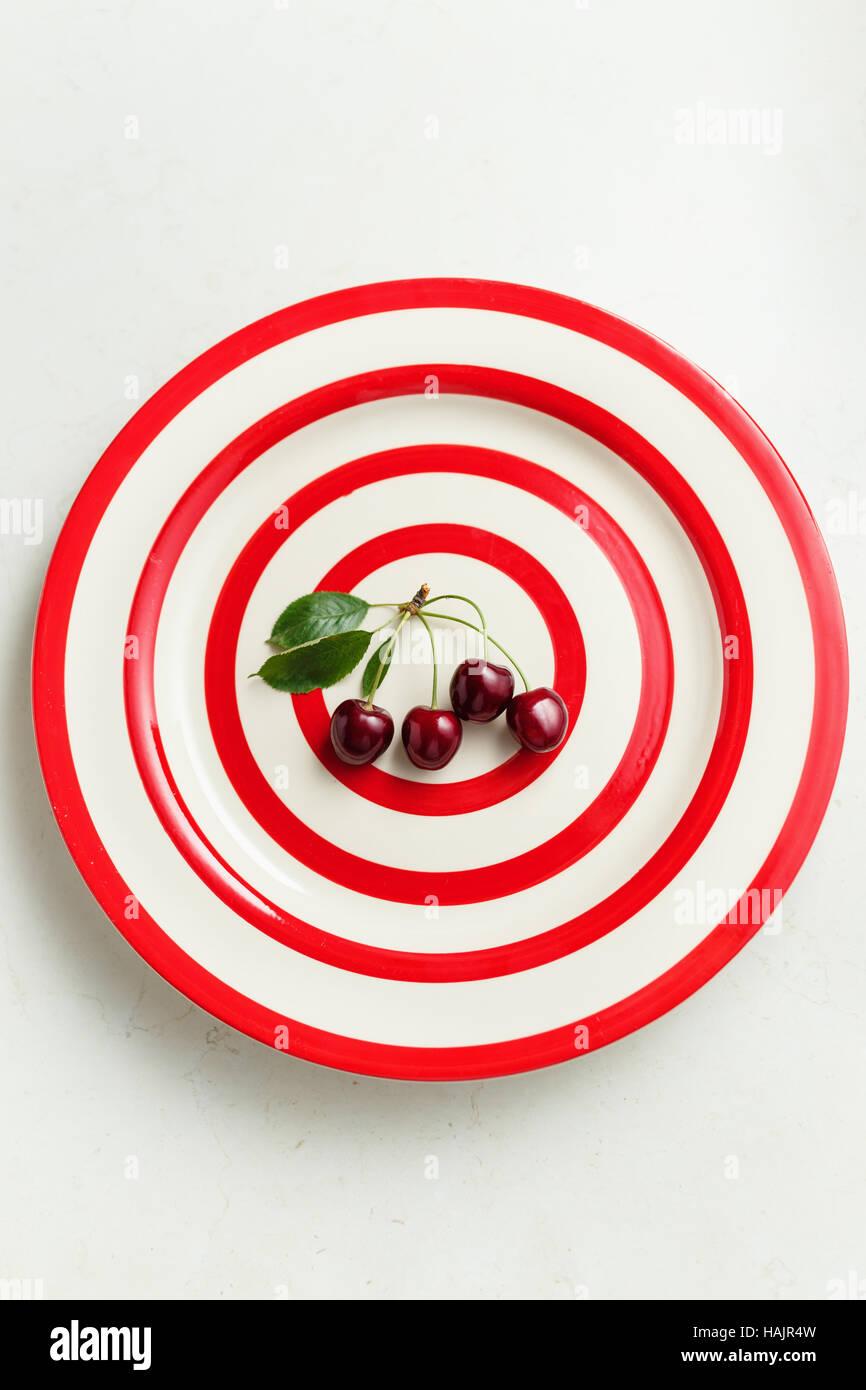 Dark red summer cherries on plate - Stock Image
