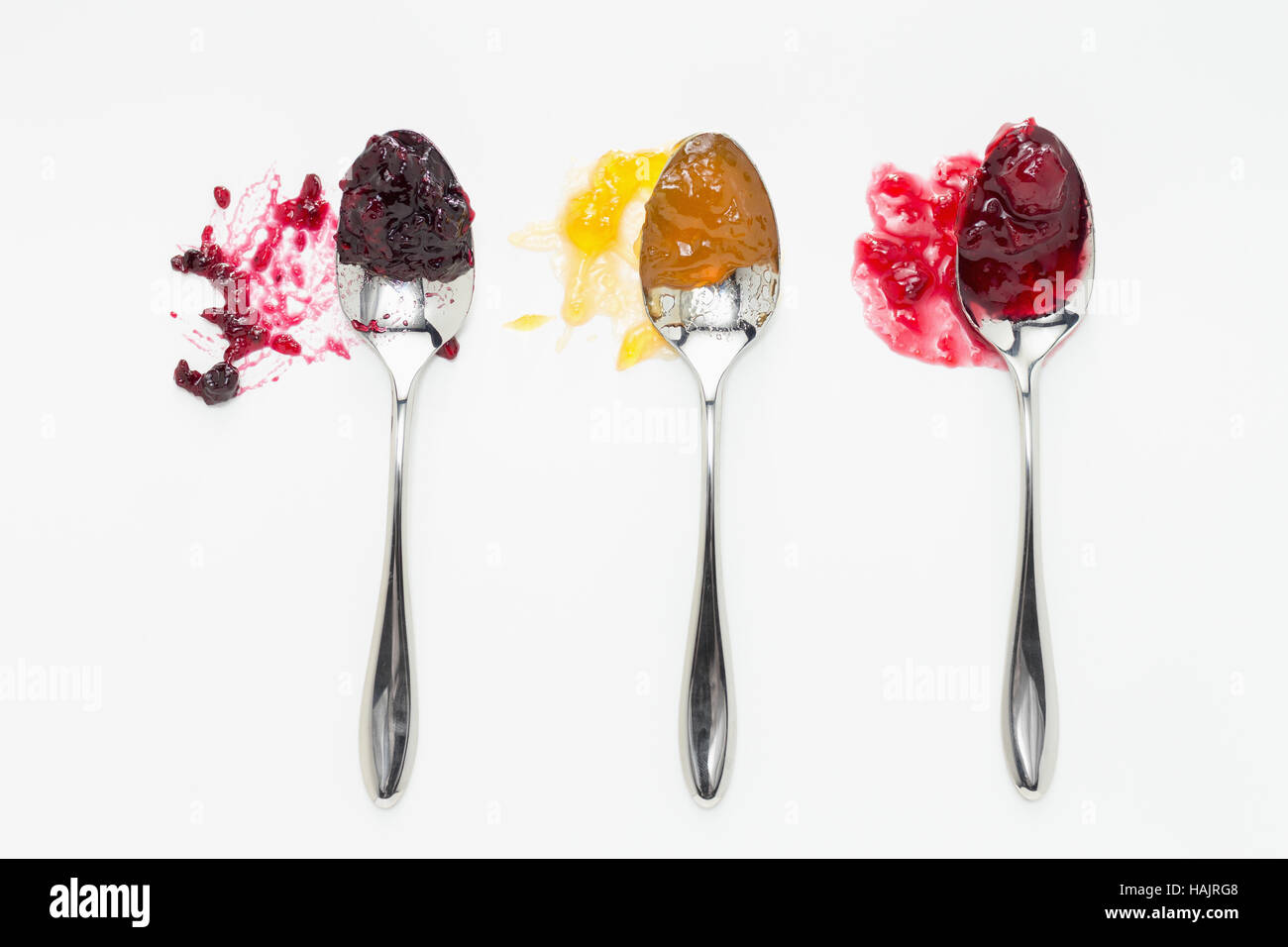 Mixed berry, apricot and sour cherry jam on spoons - Stock Image