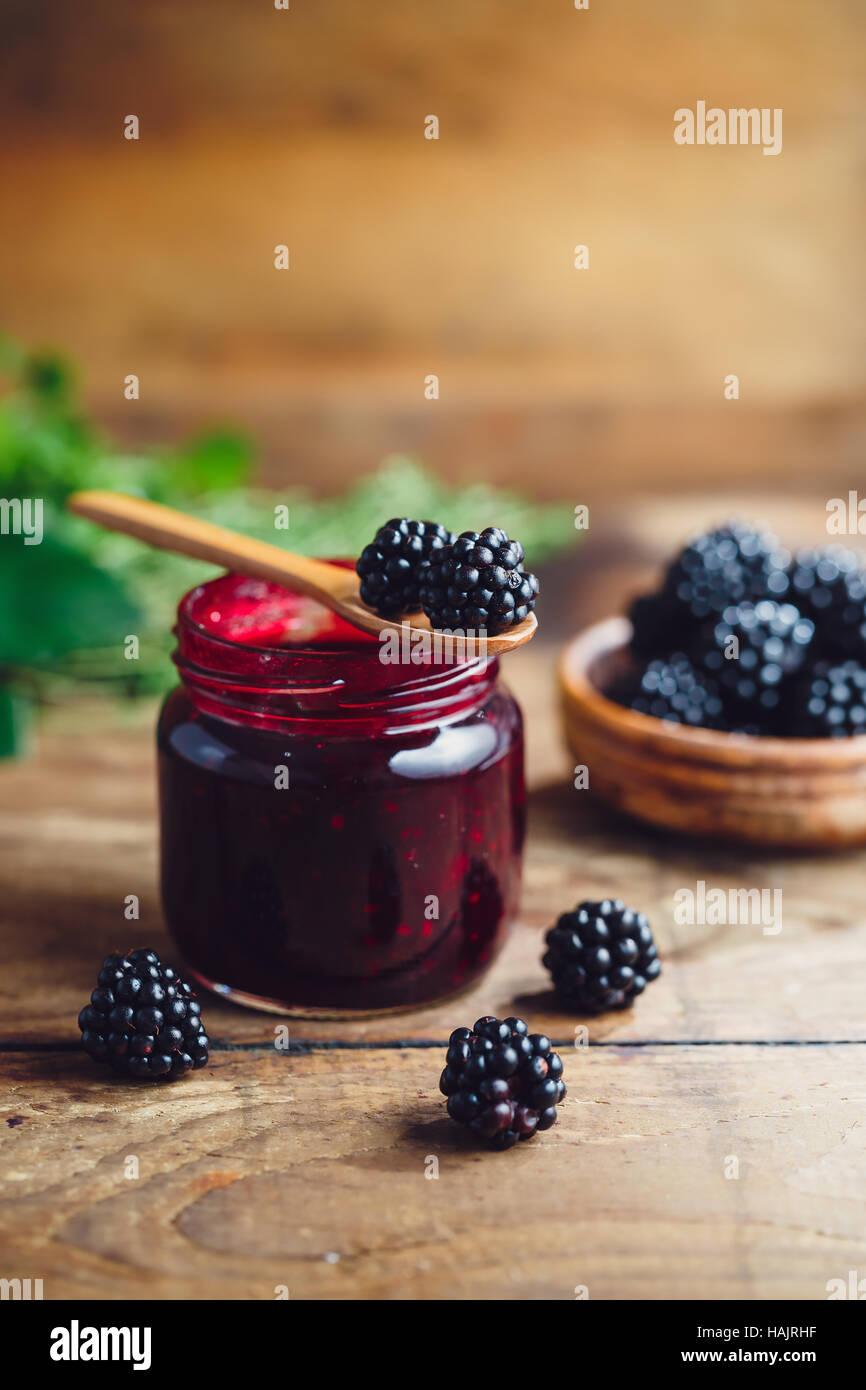Fresh homemade blackberry jam in glass jar on a wooden background - Stock Image