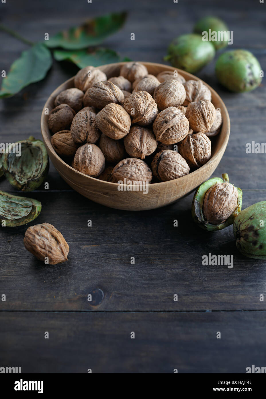 Bowl full of walnuts on wooden table - Stock Image