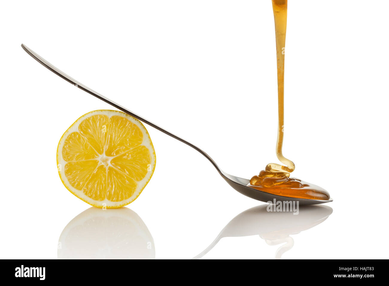 Lemon slice and honey flowing on spoon Stock Photo