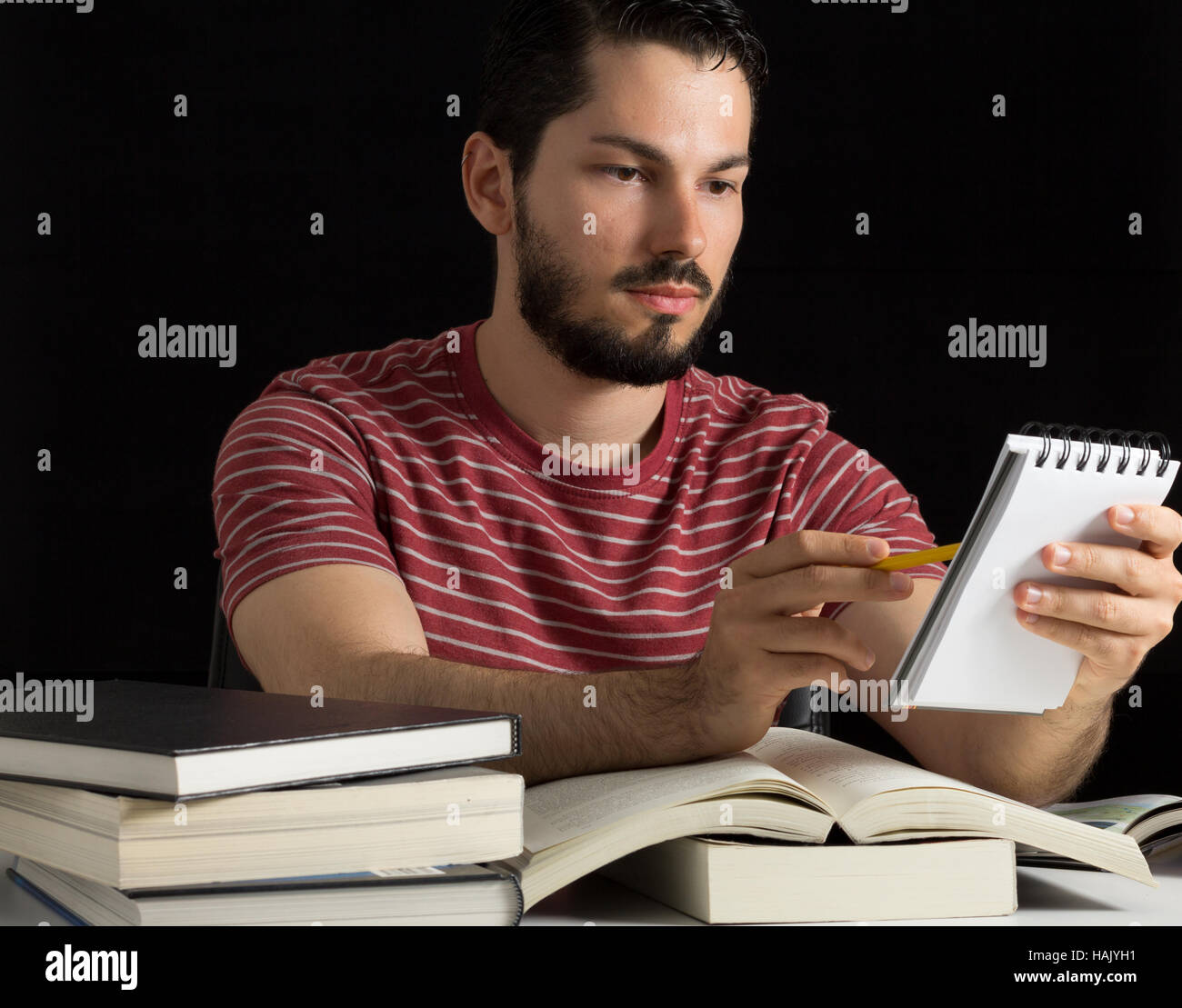 Young male reviwing personal notes during studies - Stock Image