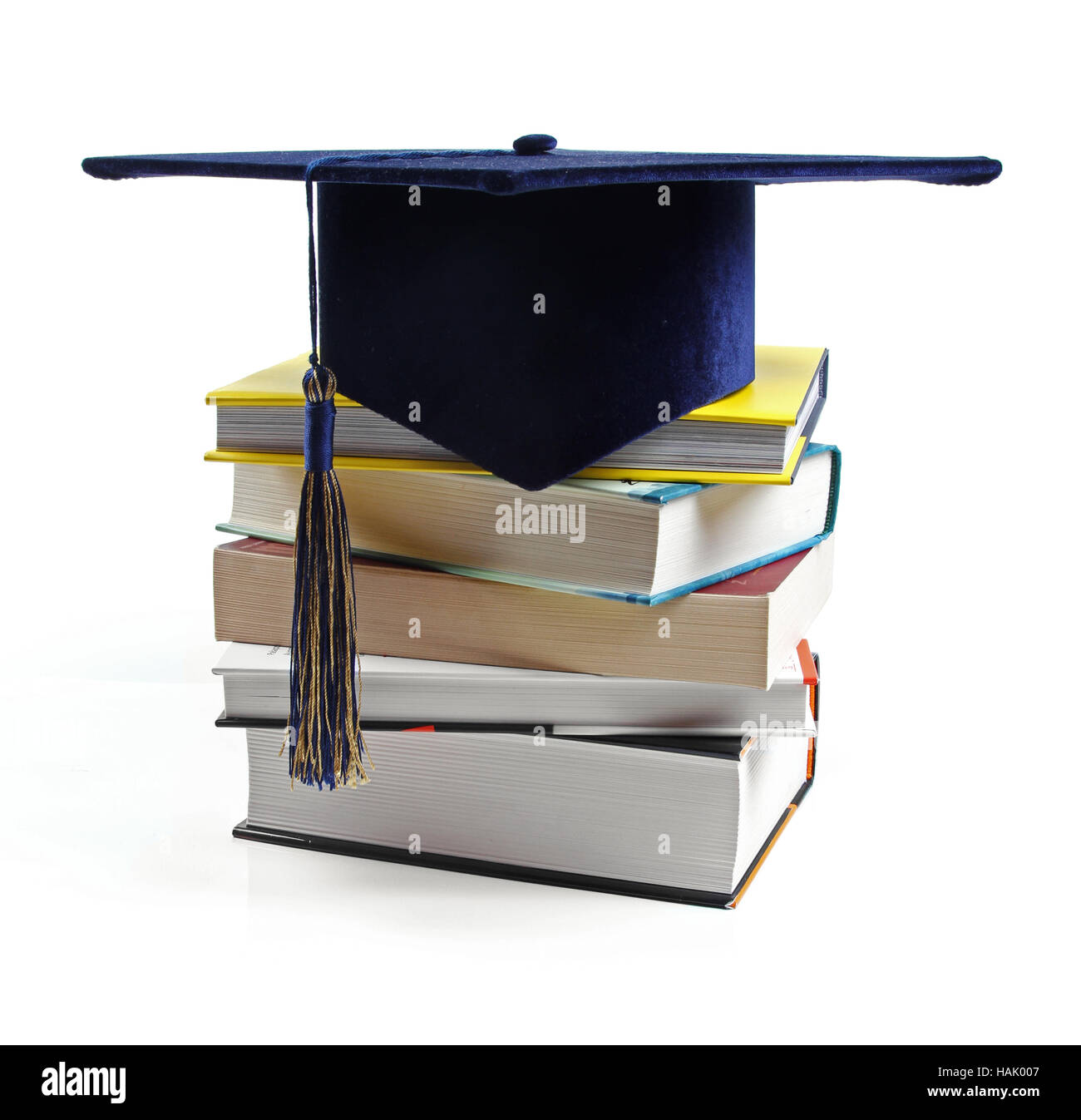 graduation hat and stack of books isolated on white - Stock Image