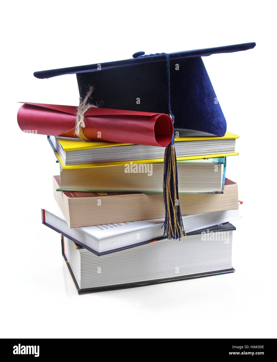 graduation hat and diploma on stack of books - Stock Image