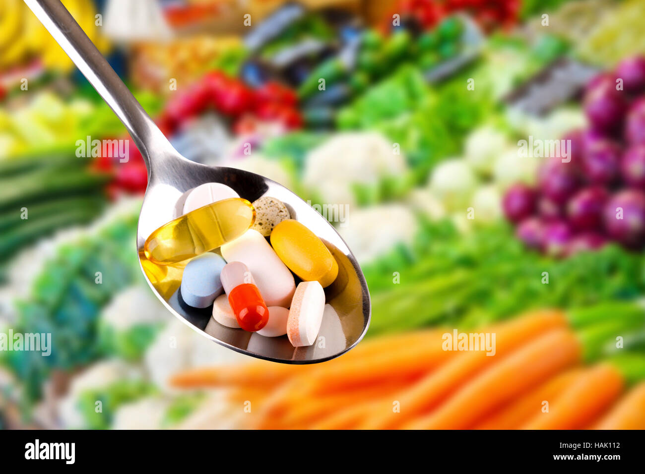 spoon with pills, dietary supplements on vegetables background - Stock Image