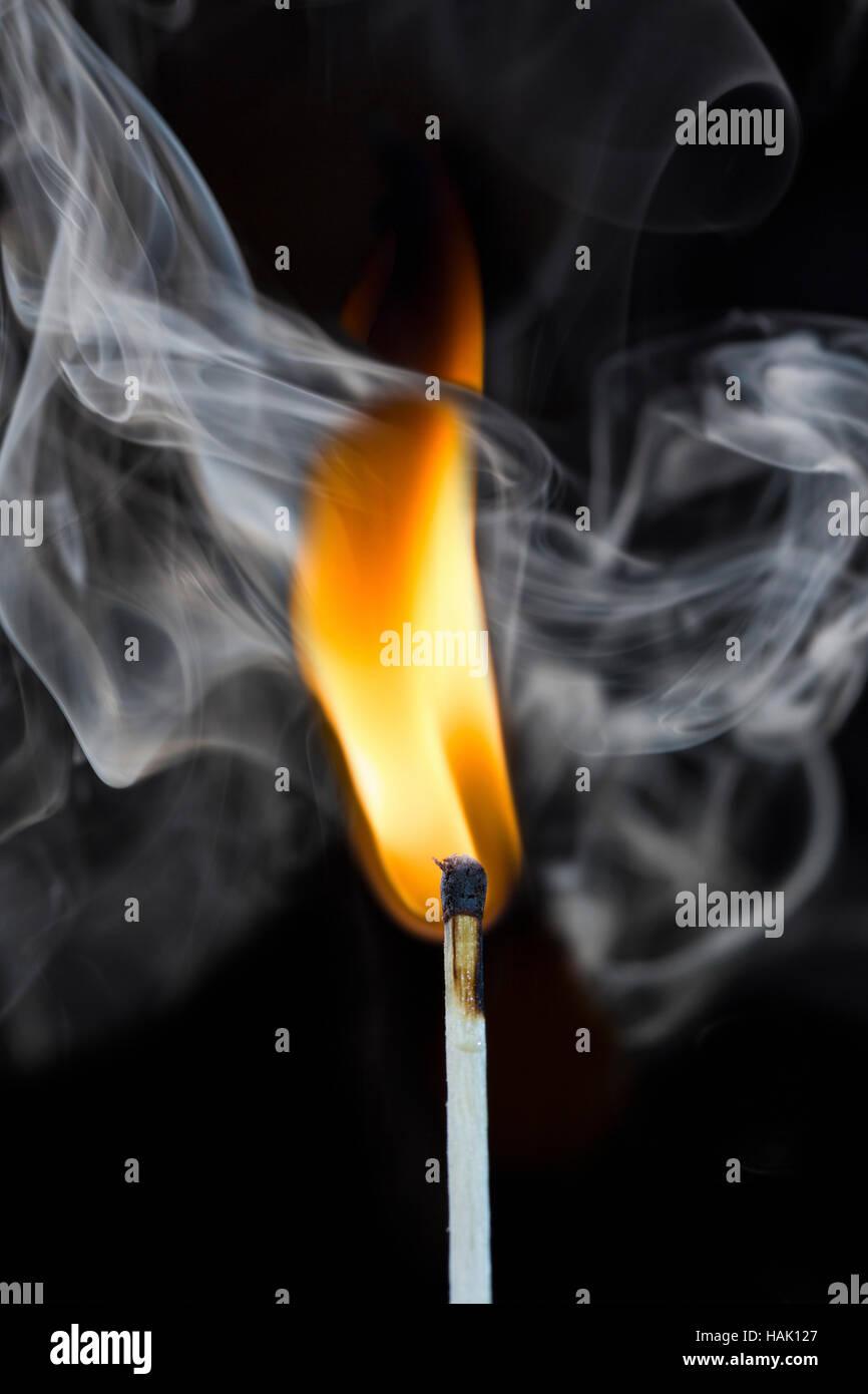 burning match with smoke on black - Stock Image