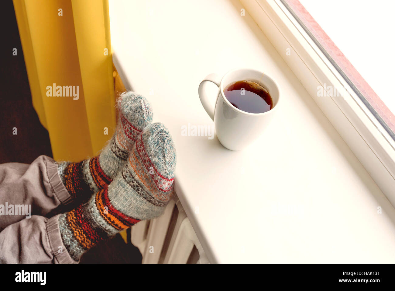 warming by the radiator and drinking hot tea Stock Photo