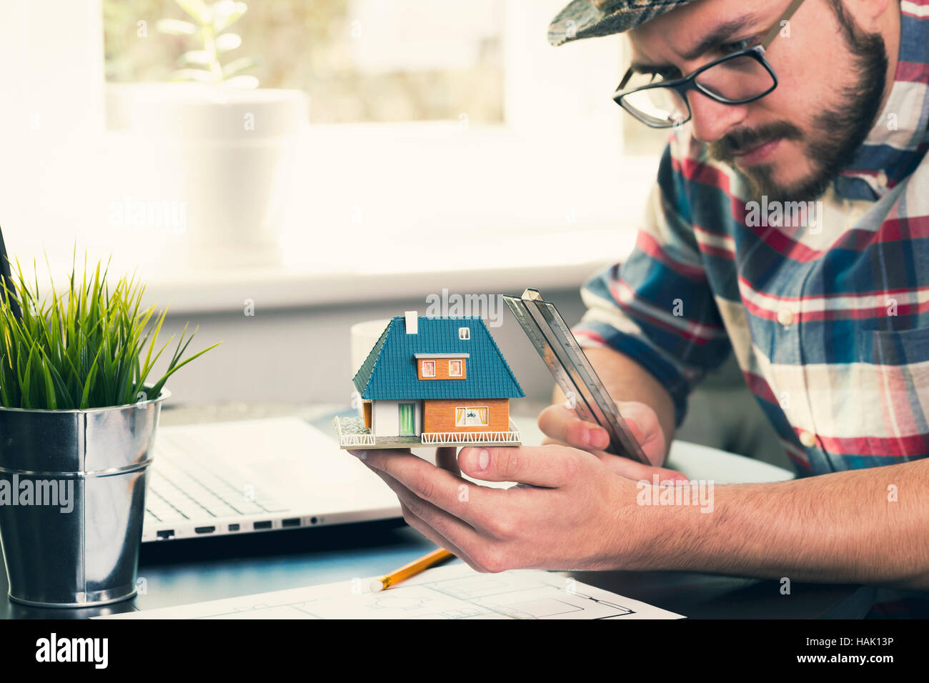 architect, construction engineer taking measurements of new house project at office - Stock Image