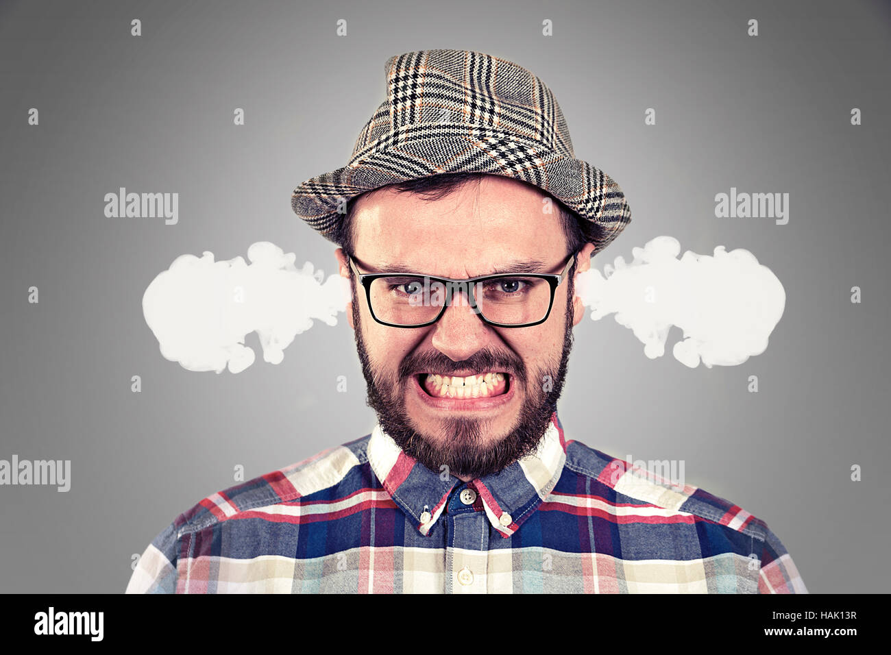 angry young man blowing steam coming out of ears - Stock Image