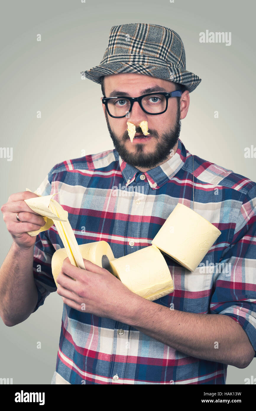 runny nose - unhappy sick man with tissues in nose - Stock Image