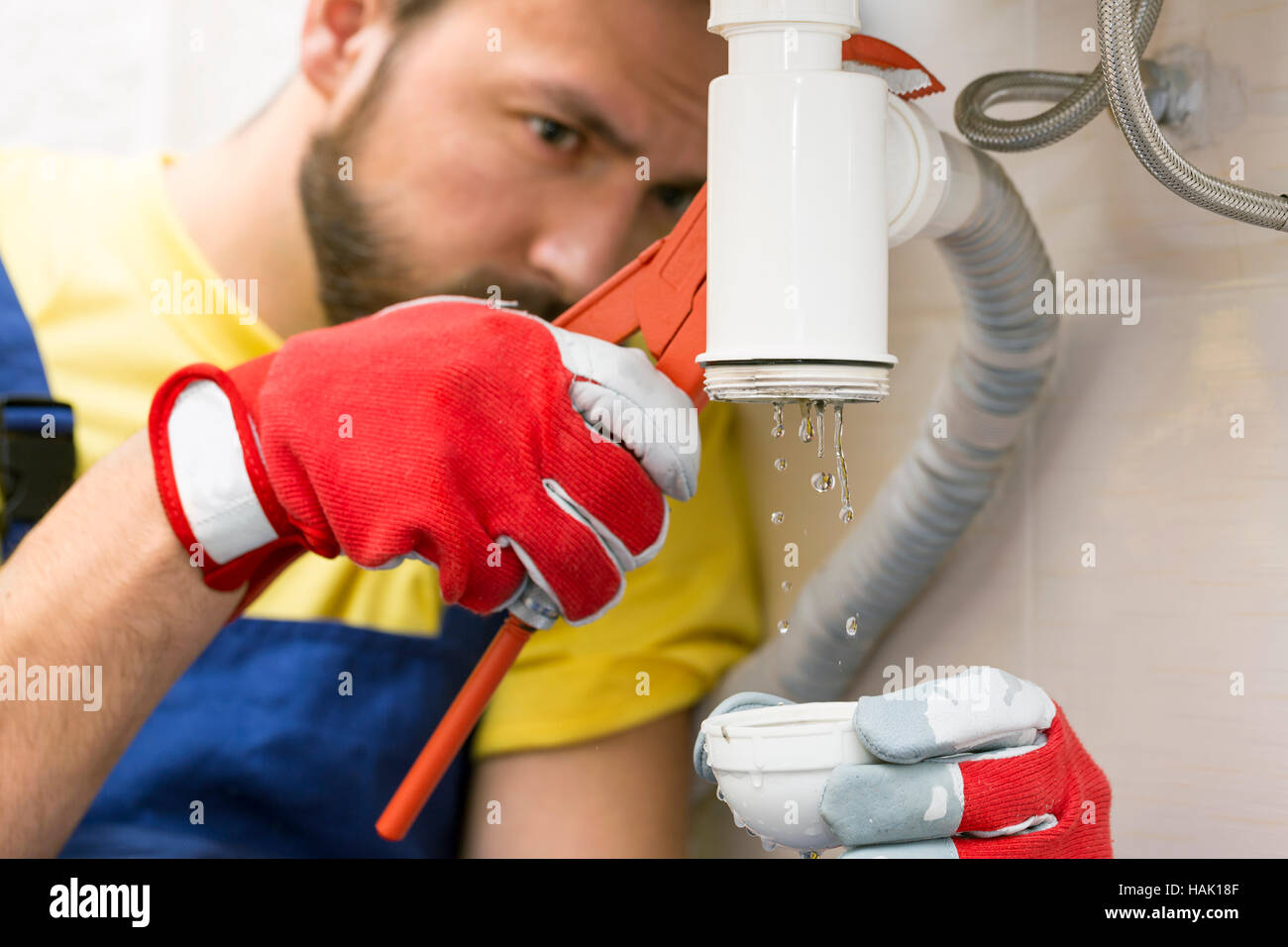 plumber fixing the sink siphon in a bathroom or kitchen - Stock Image
