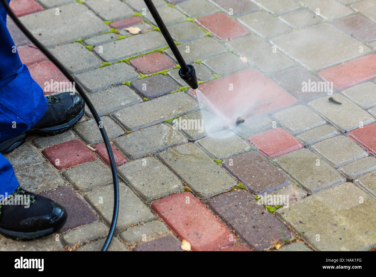 pavement cleaning with high pressure washer - Stock Image