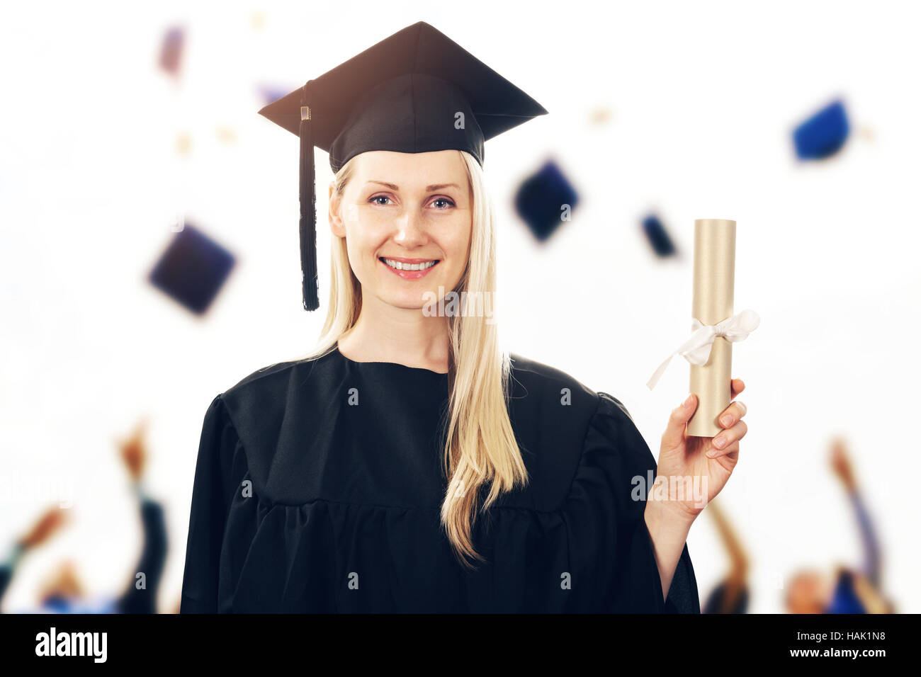 college graduation - woman wearing gown showing diploma - Stock Image