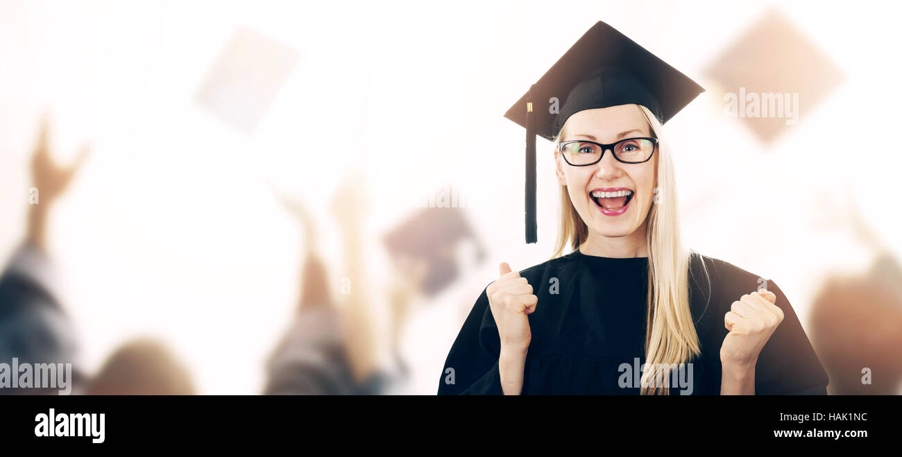 graduation - happy graduate wearing gown and hat with copyspace - Stock Image