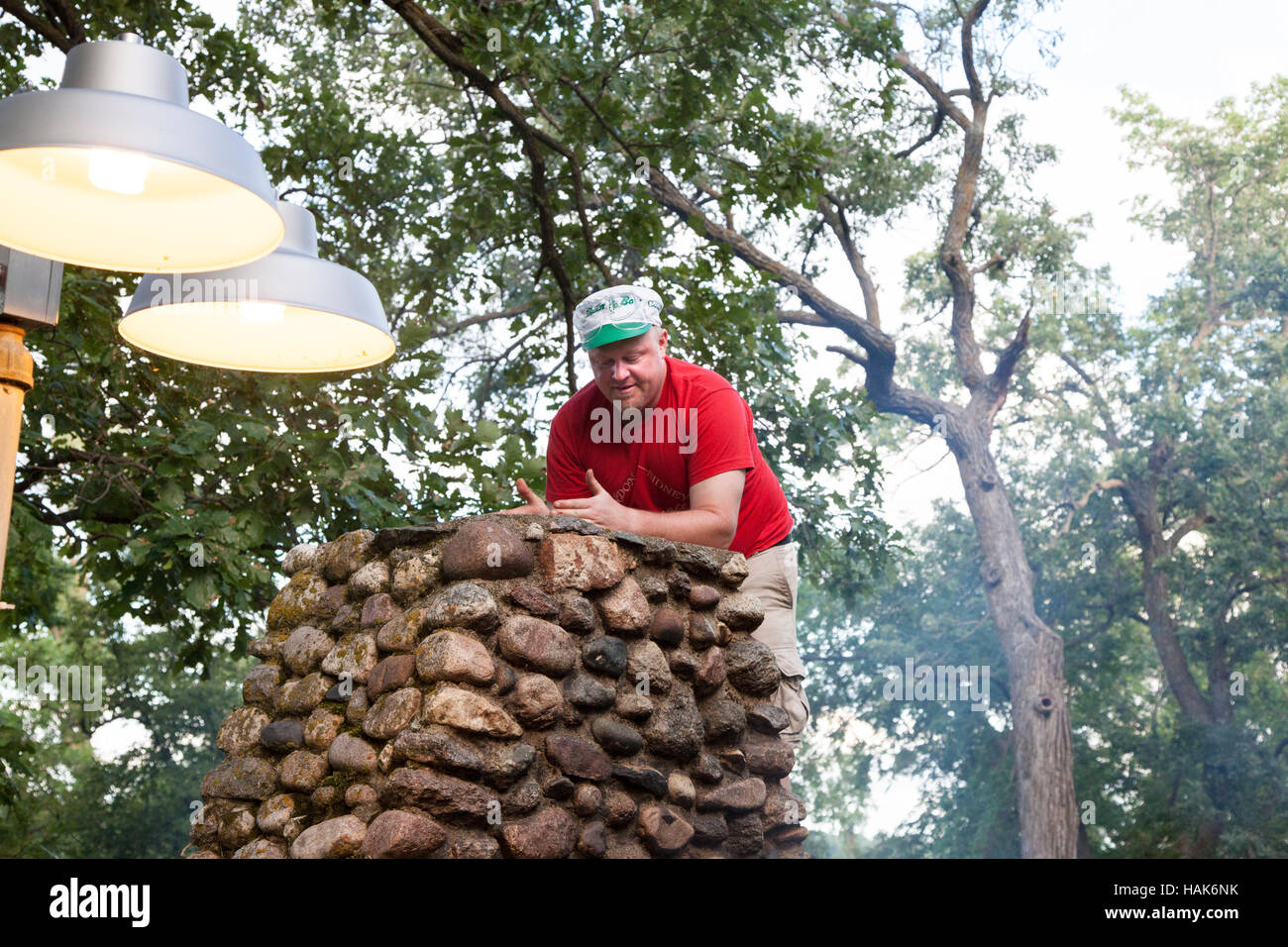 Man age 37 inspecting his out door fieldstone barbecue fireplace for chimney clogging soot. Clitherall Minnesota - Stock Image
