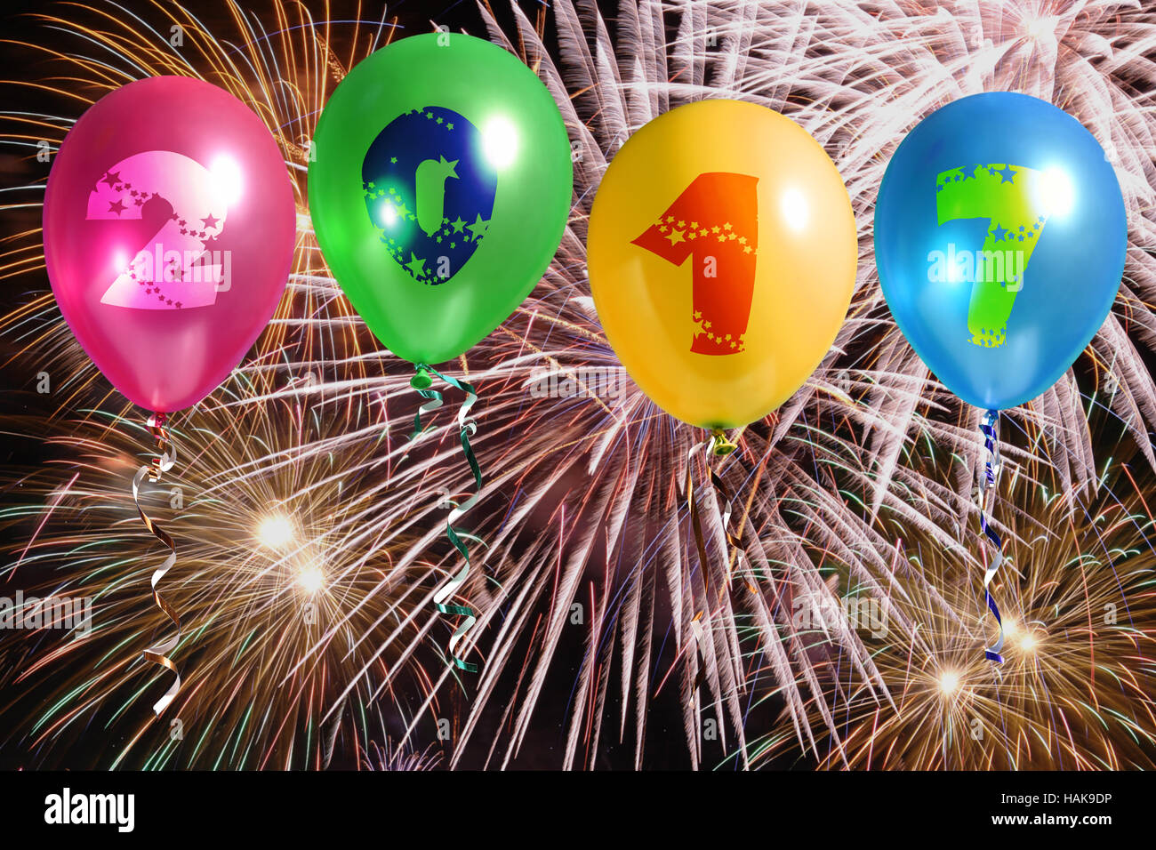 Four colorful balloons with 2017 New Year digits against fireworks - Stock Image